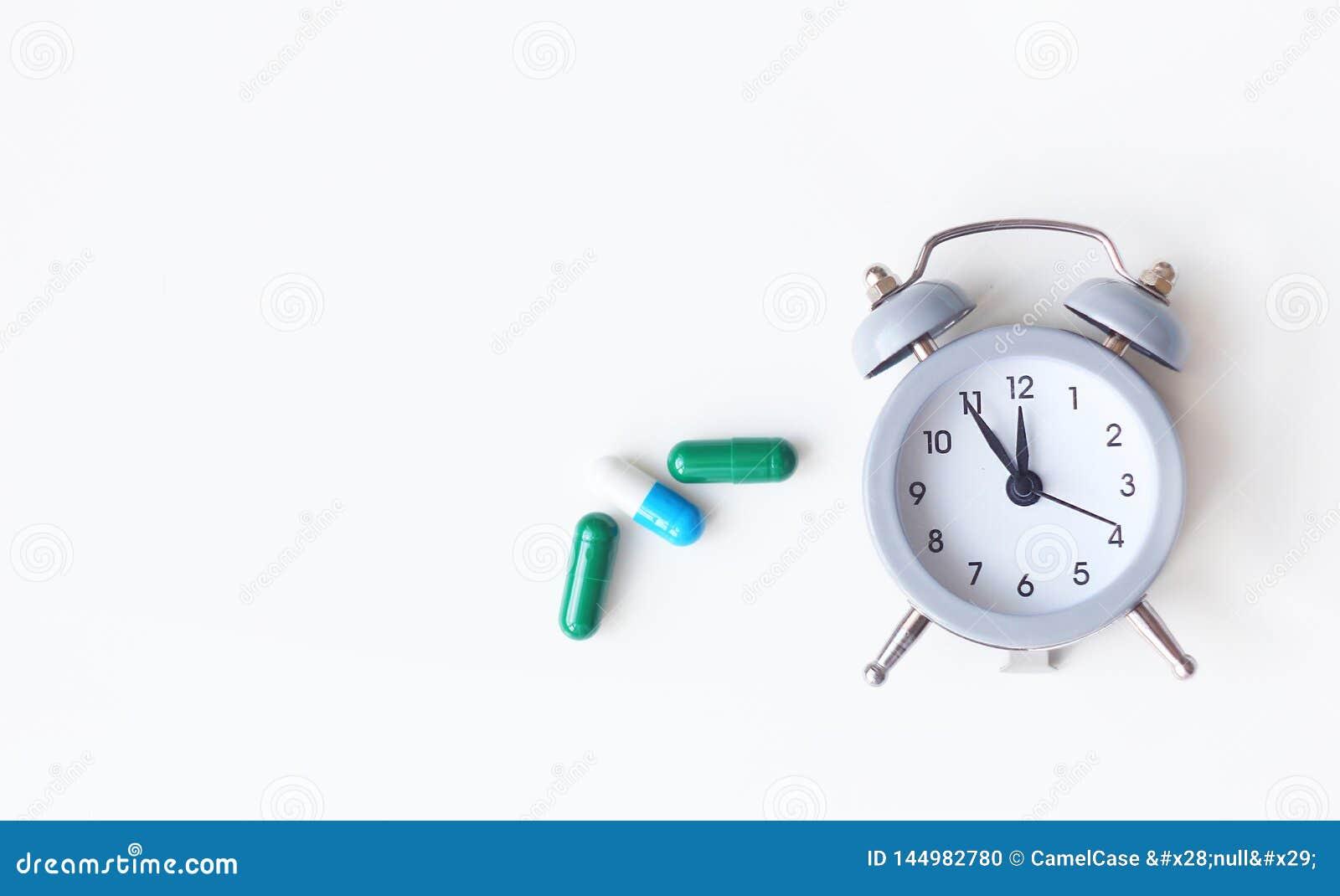 闹钟和医疗药片在白色背景