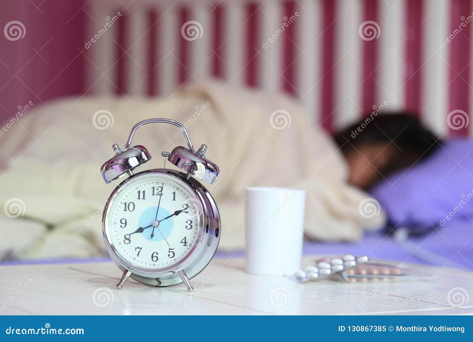 闹钟和杯水,与睡觉的妇女的医学