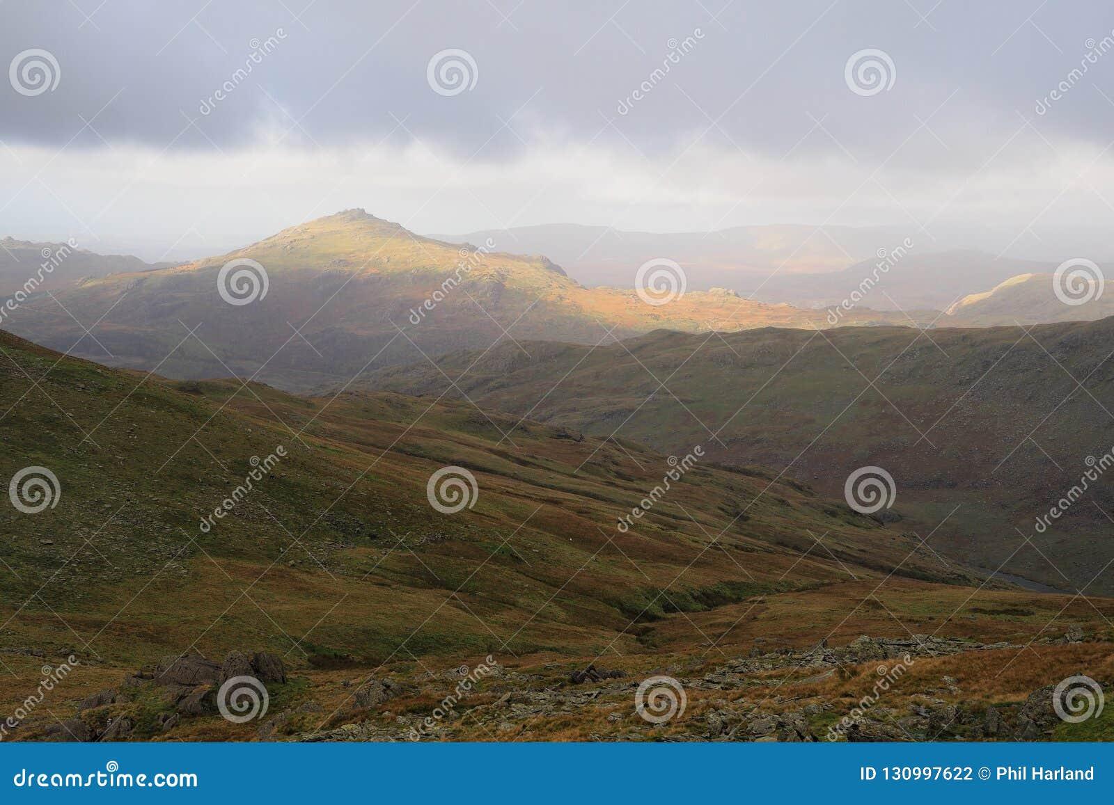 阳光在湖区山上面落在打开它的阴云密布和多云天空外面与温暖的秋天颜色