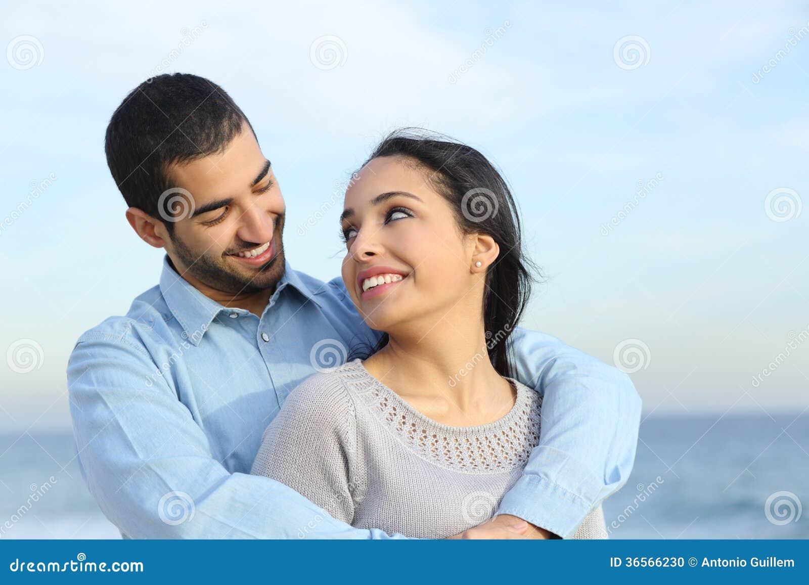 阿拉伯偶然夫妇拥抱满意对在海滩的爱
