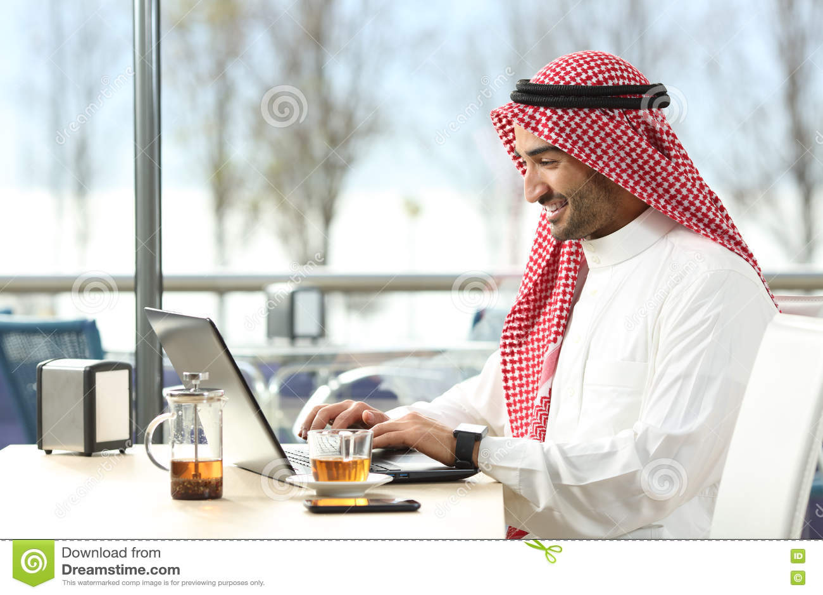 阿拉伯沙特人在网上与膝上型计算机一起使用