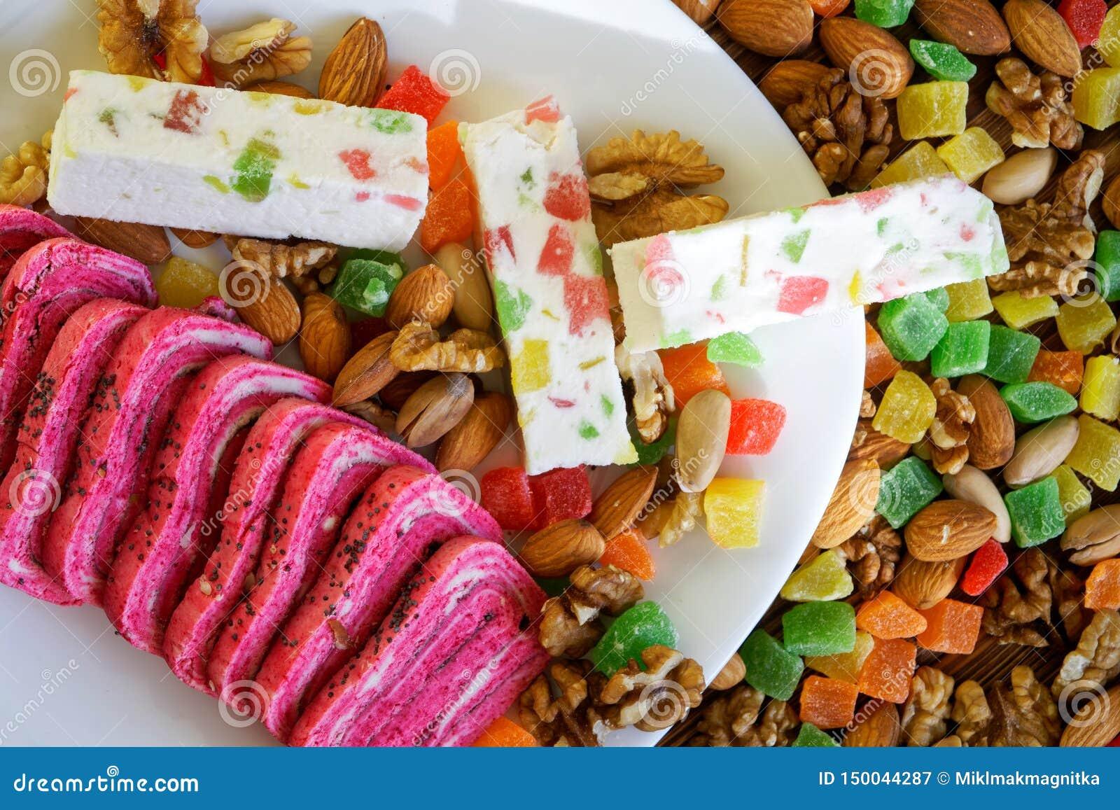 阿拉伯甜点:异常的桃红色halva和白色喉片在脯、开心果、杏仁和核桃旁边 全国东方人