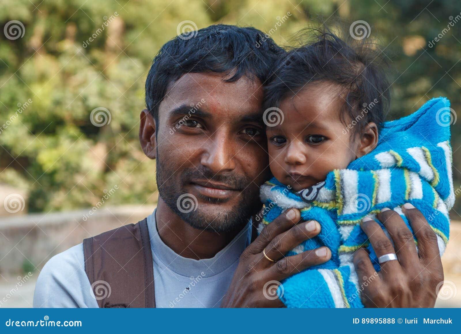 阿格拉,印度- 2012年12月:印地安家庭,拿着他的膝部的父亲女儿
