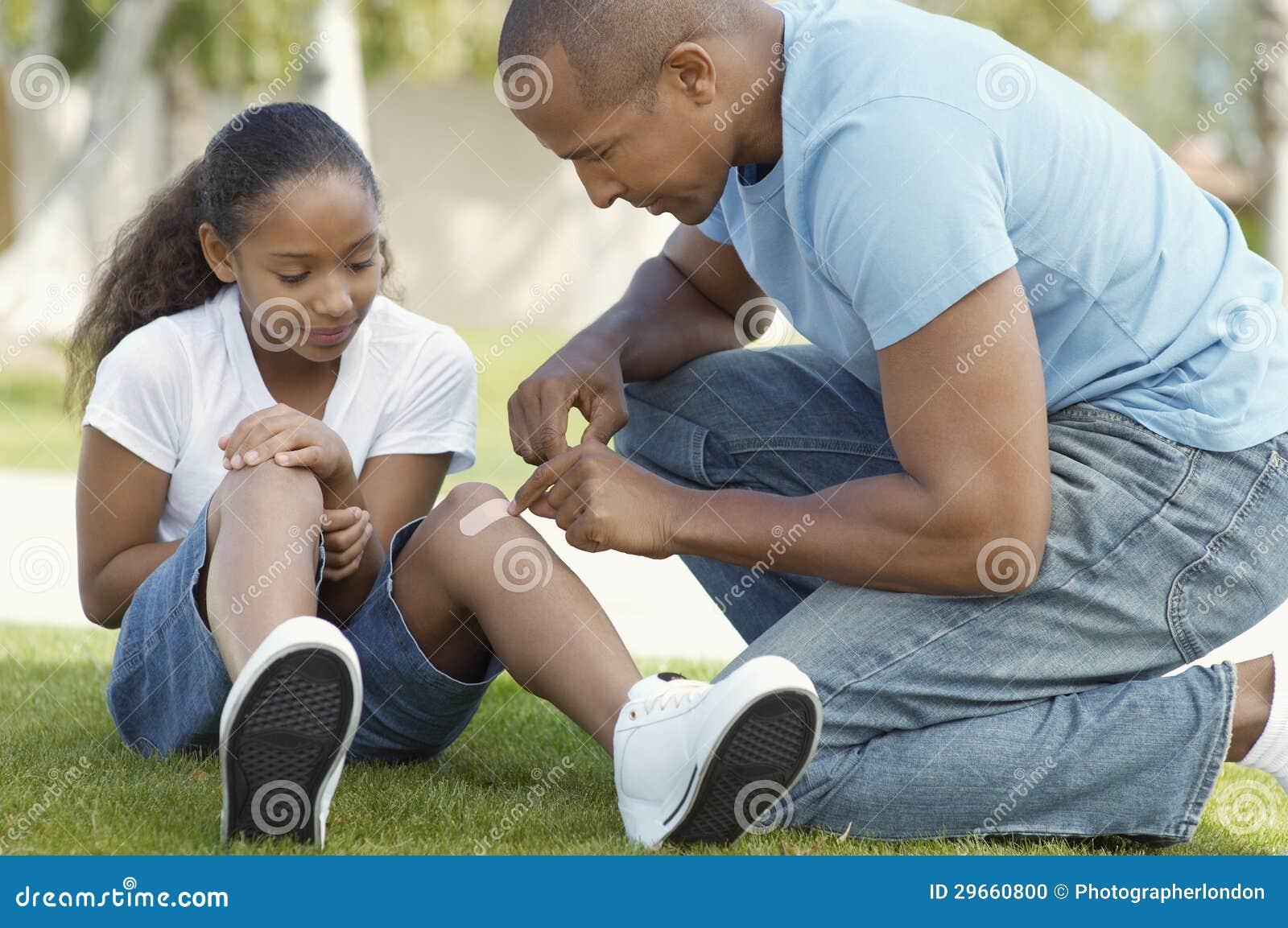 黏附绷带的父亲对女儿的膝盖在公园