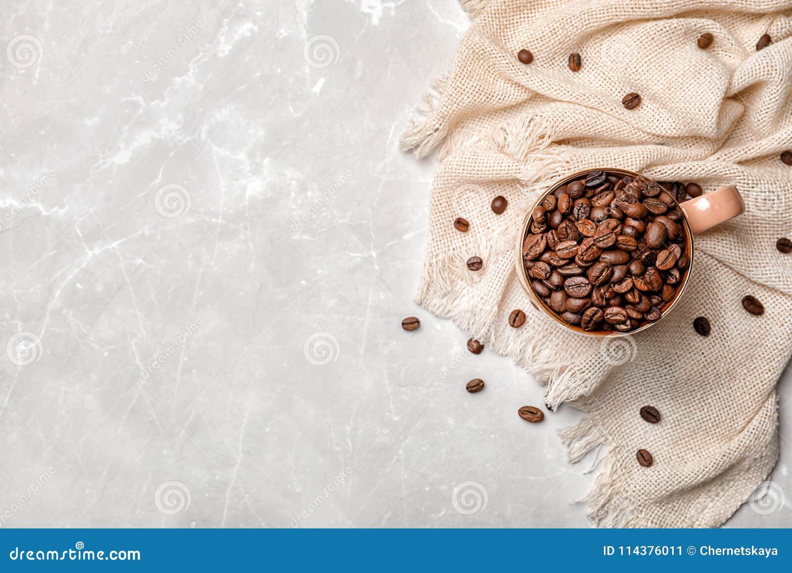 陶瓷杯子用在轻的背景的咖啡豆