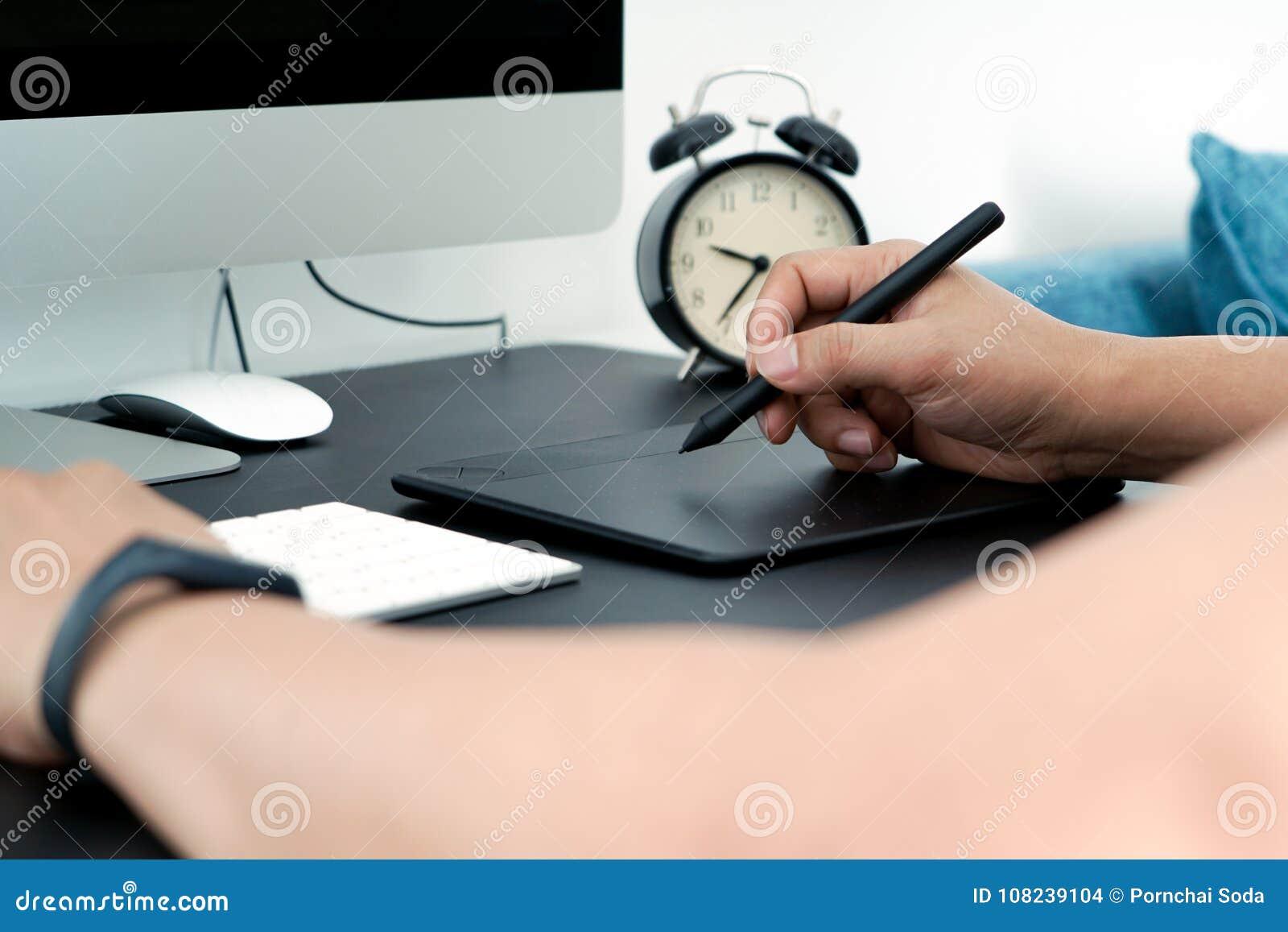集中于研究计算机的繁忙的图表设计师在数字式笔老鼠旁边