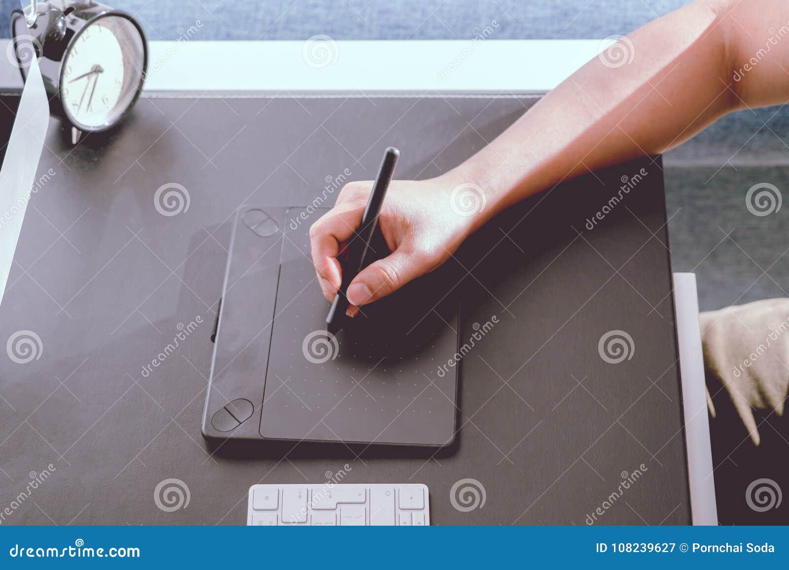集中于研究计算机的繁忙的图表设计师在数字式笔老鼠,噪声滤波器旁边申请