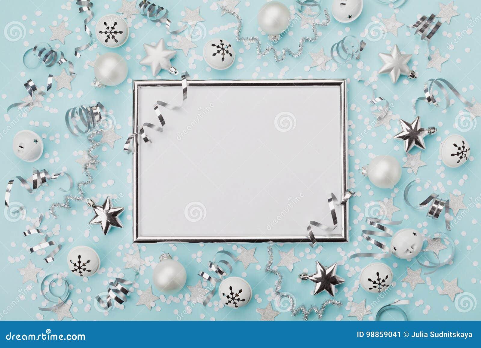 集会与五彩纸屑、球和星的狂欢节圣诞节背景装饰的银色框架在绿松石桌面视图 平的位置