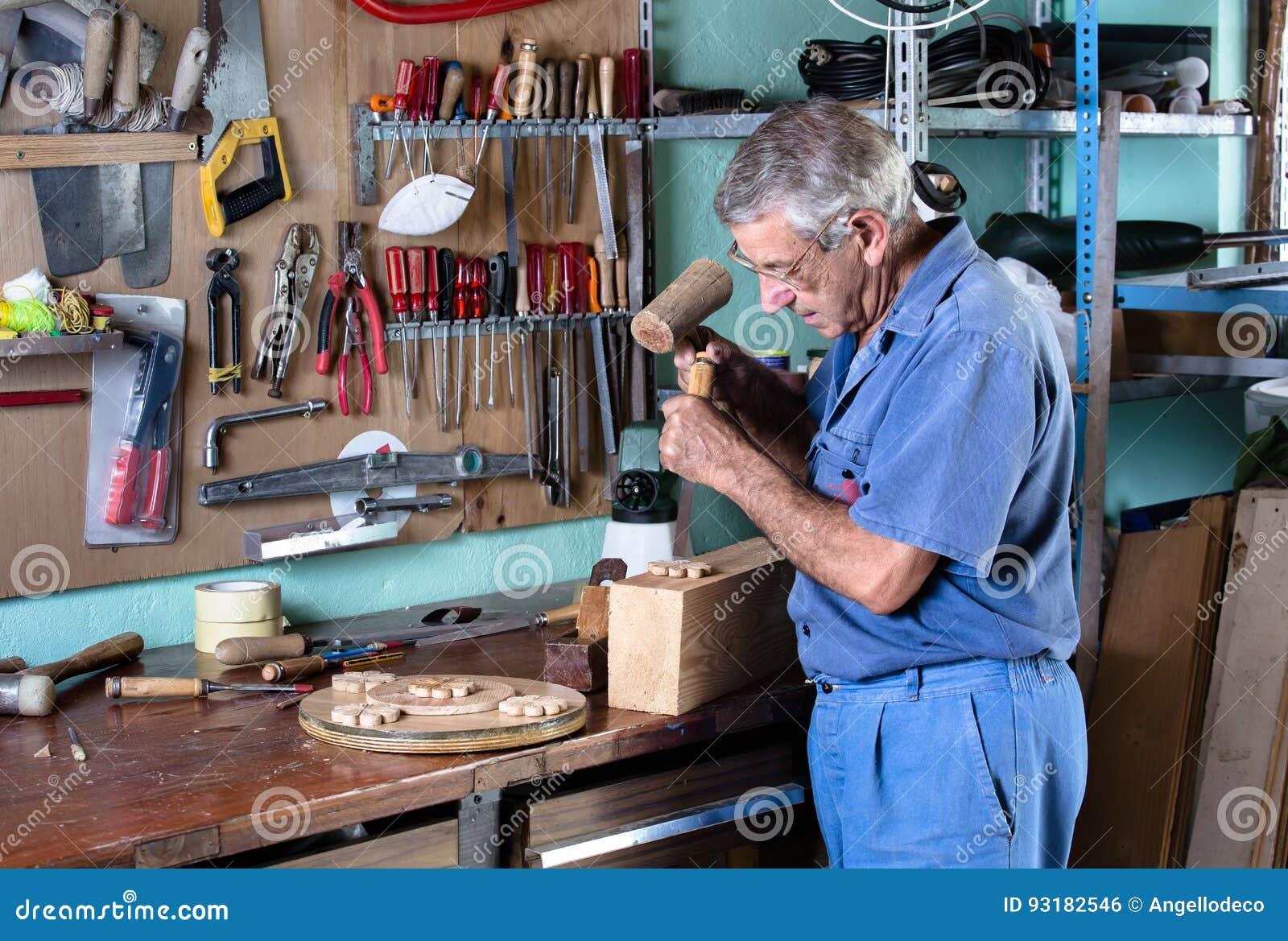 雕刻与凿子和锤子的家具工木头在工作凳