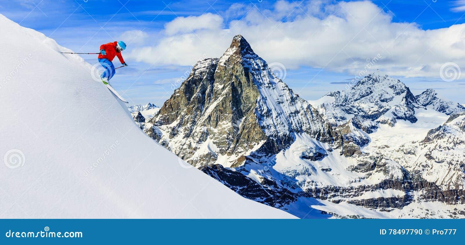 滑雪下坡在新鲜的粉末雪的高山的滑雪者 锡