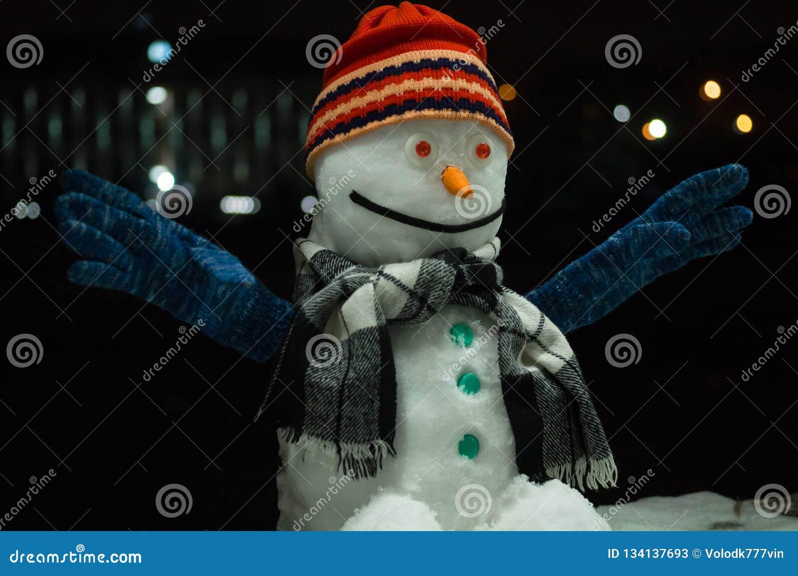 雪人 在黑暗的夜背景的滑稽的雪人,与大胆的光在背景中 新年2019年