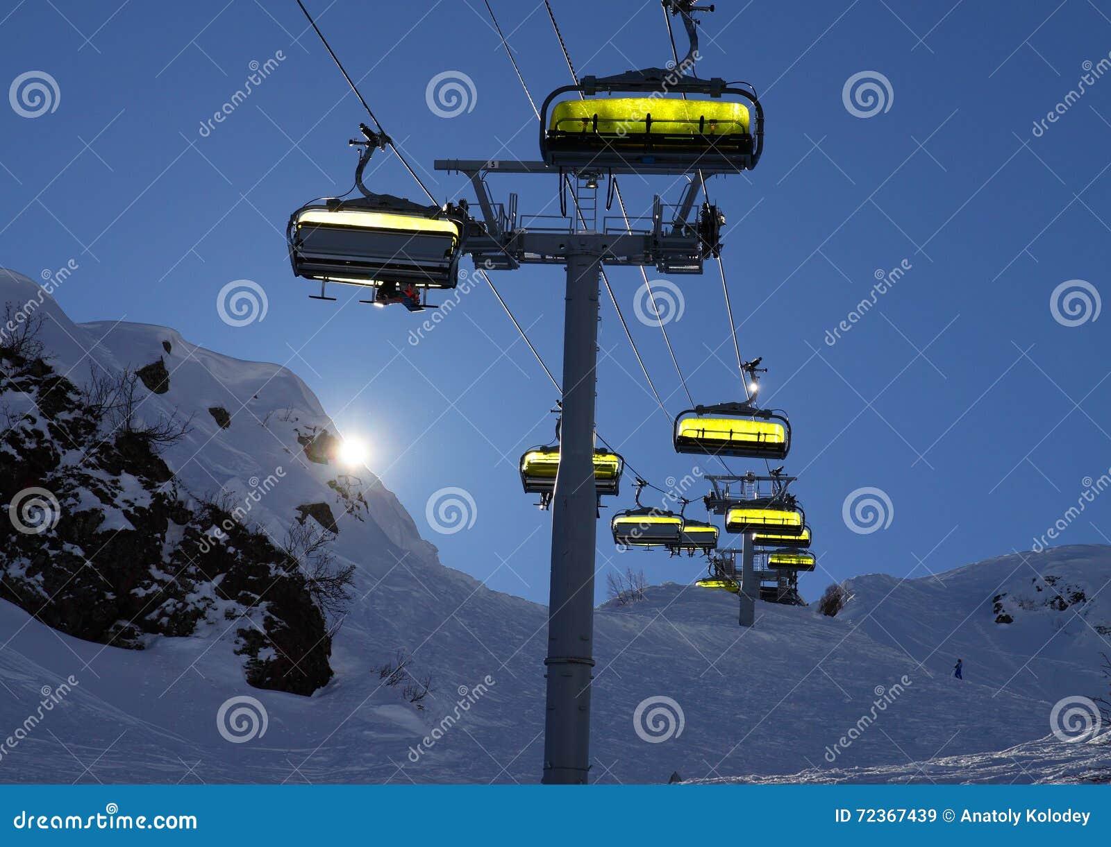 滑雪电缆车由后照与明亮的太阳