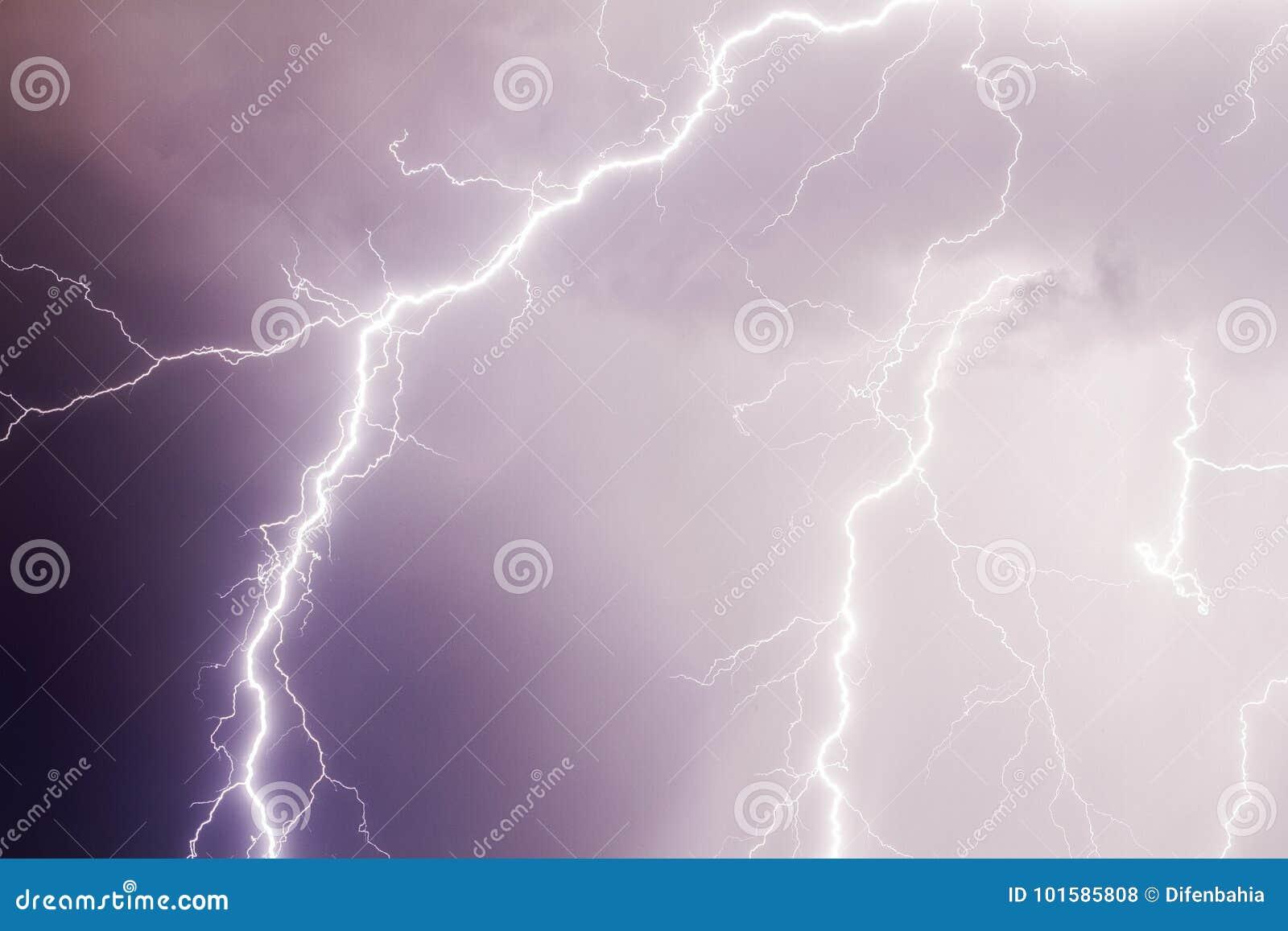雷暴在黑暗的紫色多云天空的雷击