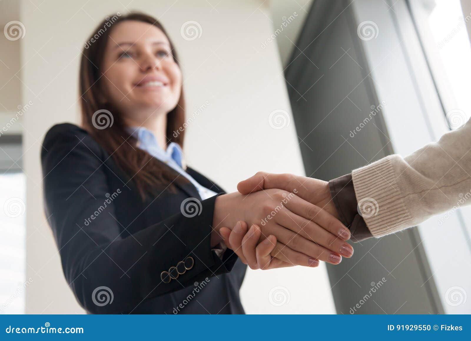 震动男性手和微笑的可爱的欢迎女实业家