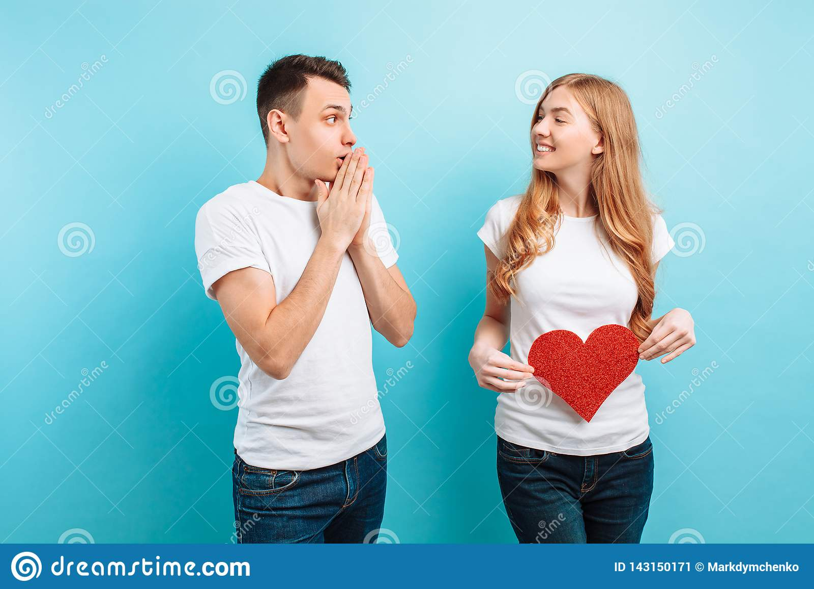 震惊人,得知他的妻子,拿着红色纸心脏的孕妇怀孕反对腹部