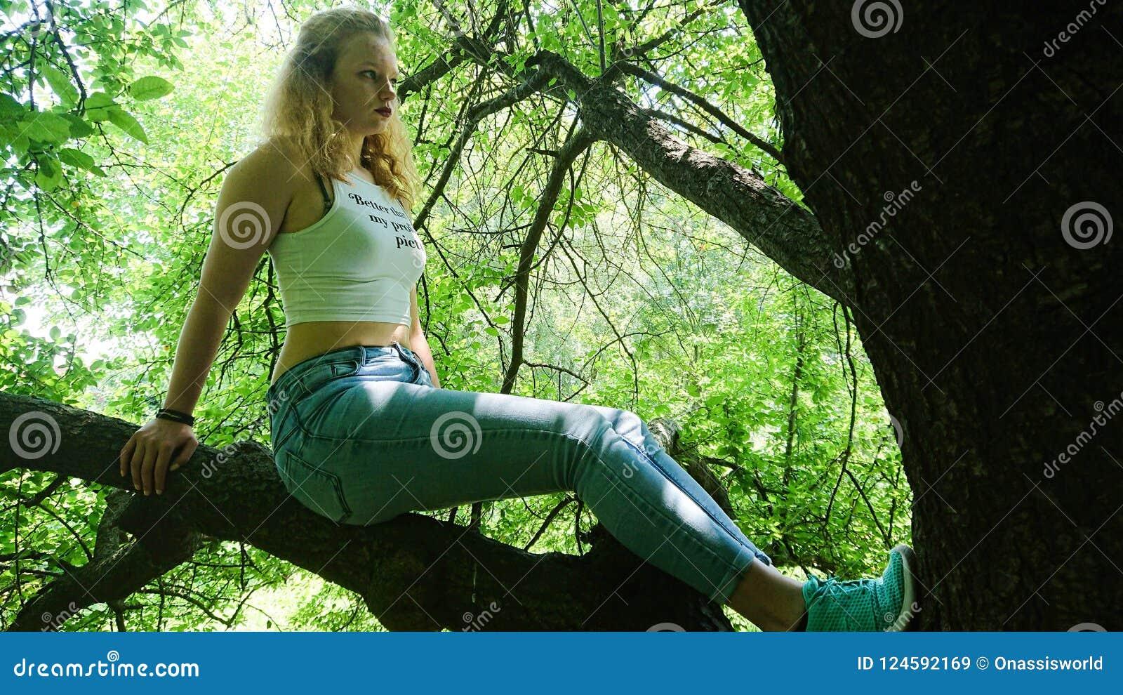 青少年摆在一个大树枝在一个晴天