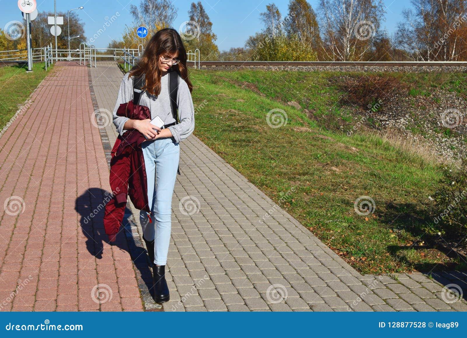 青少年的女孩佩带的玻璃和牛仔裤走的街道