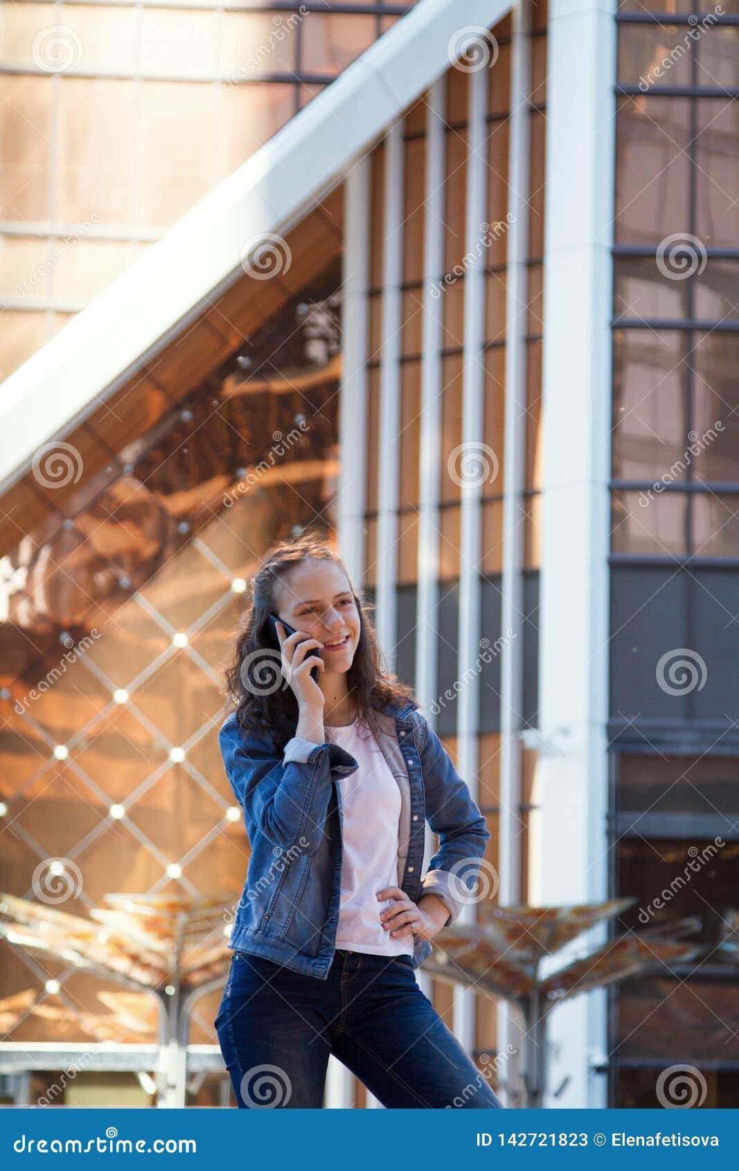 青少年的女孩有一次手机谈话在一个大大都会