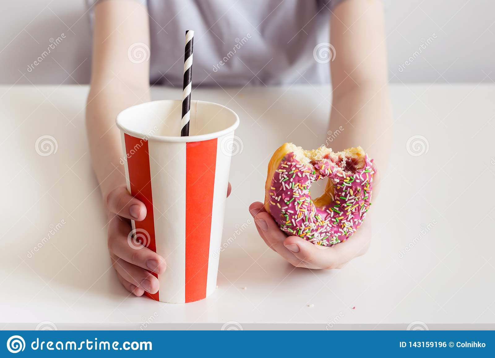 青少年的男孩藏品多福饼和甜泡沫腾涌的饮料