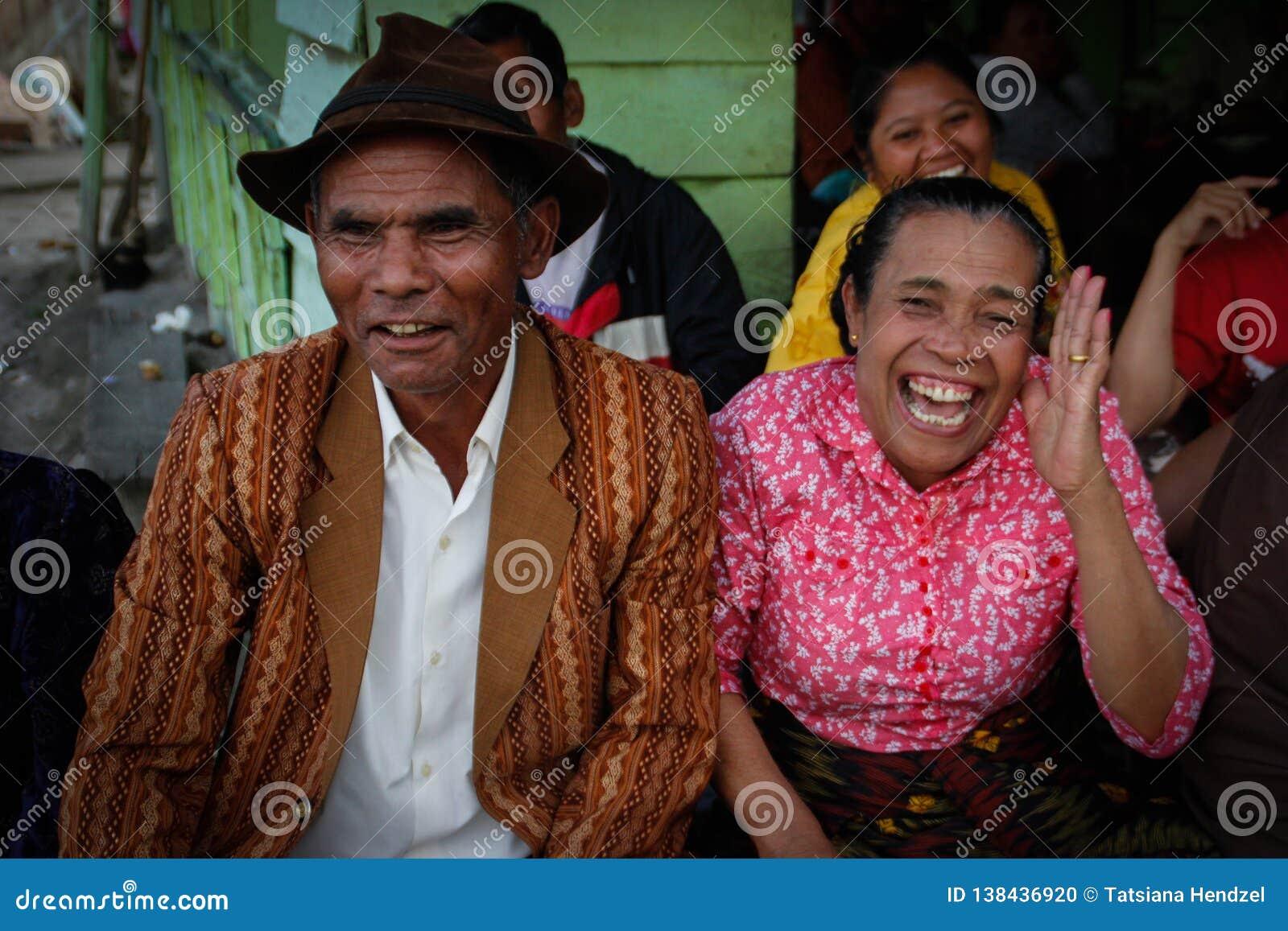 非常一件桃红色女衬衫和她时髦地加工好的人的快乐的笑的和摸索的印度尼西亚年长妇女一个棕色帽子的