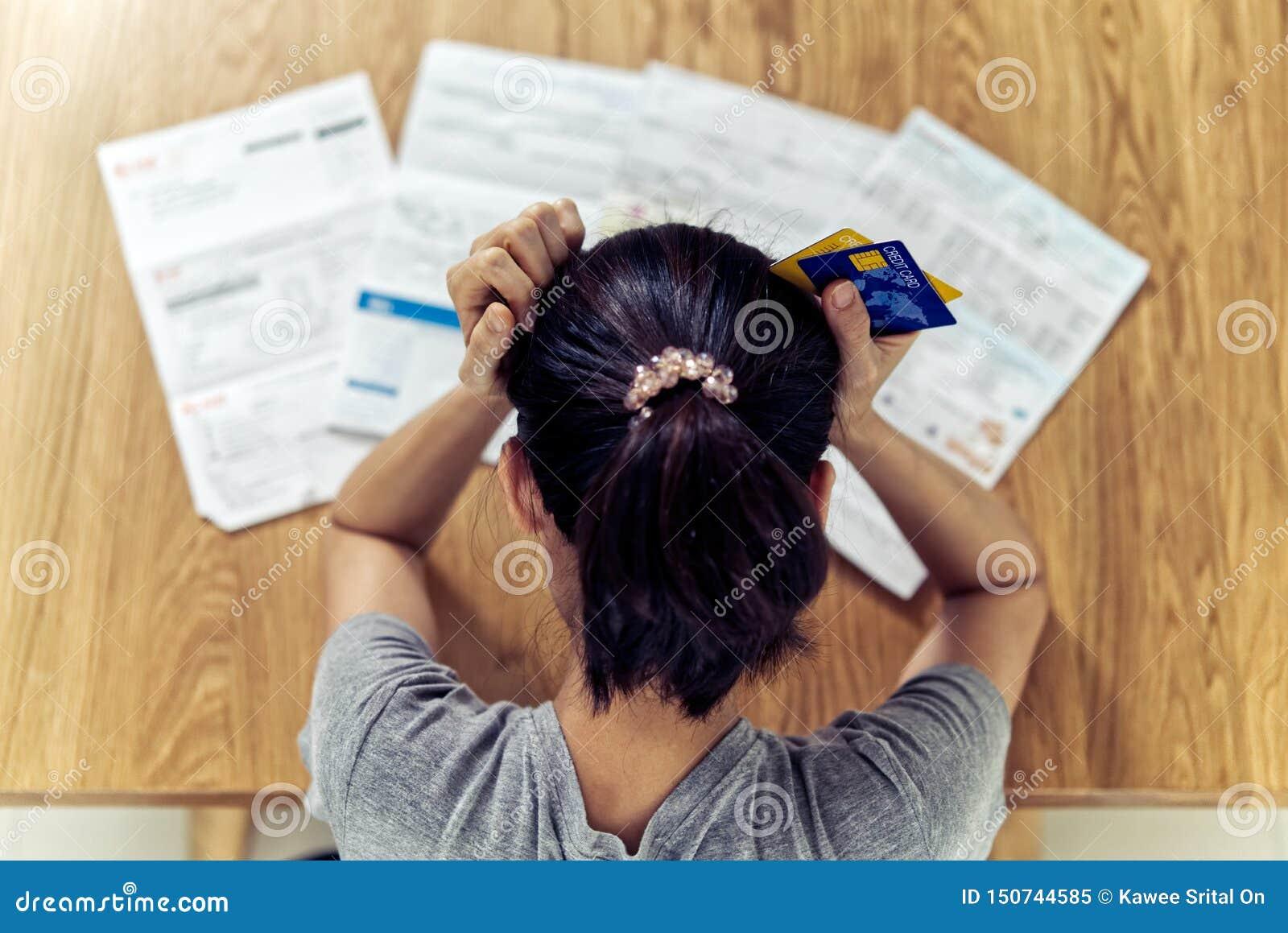 非常强调了举行对发现金钱的年轻坐的亚洲妇女手顶头忧虑支付信用卡债务