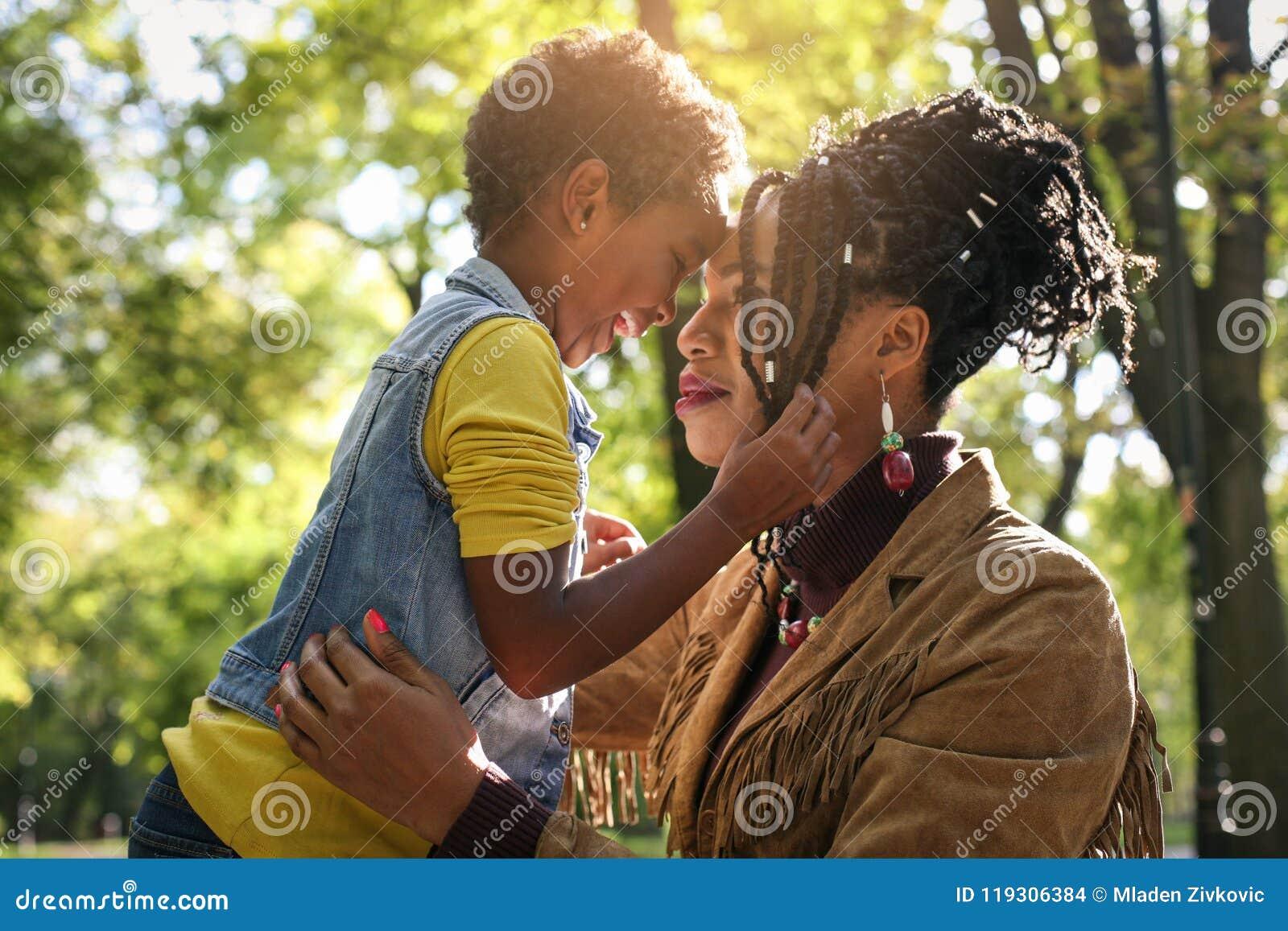 非裔美国人的单亲母亲在有她的女儿的公园
