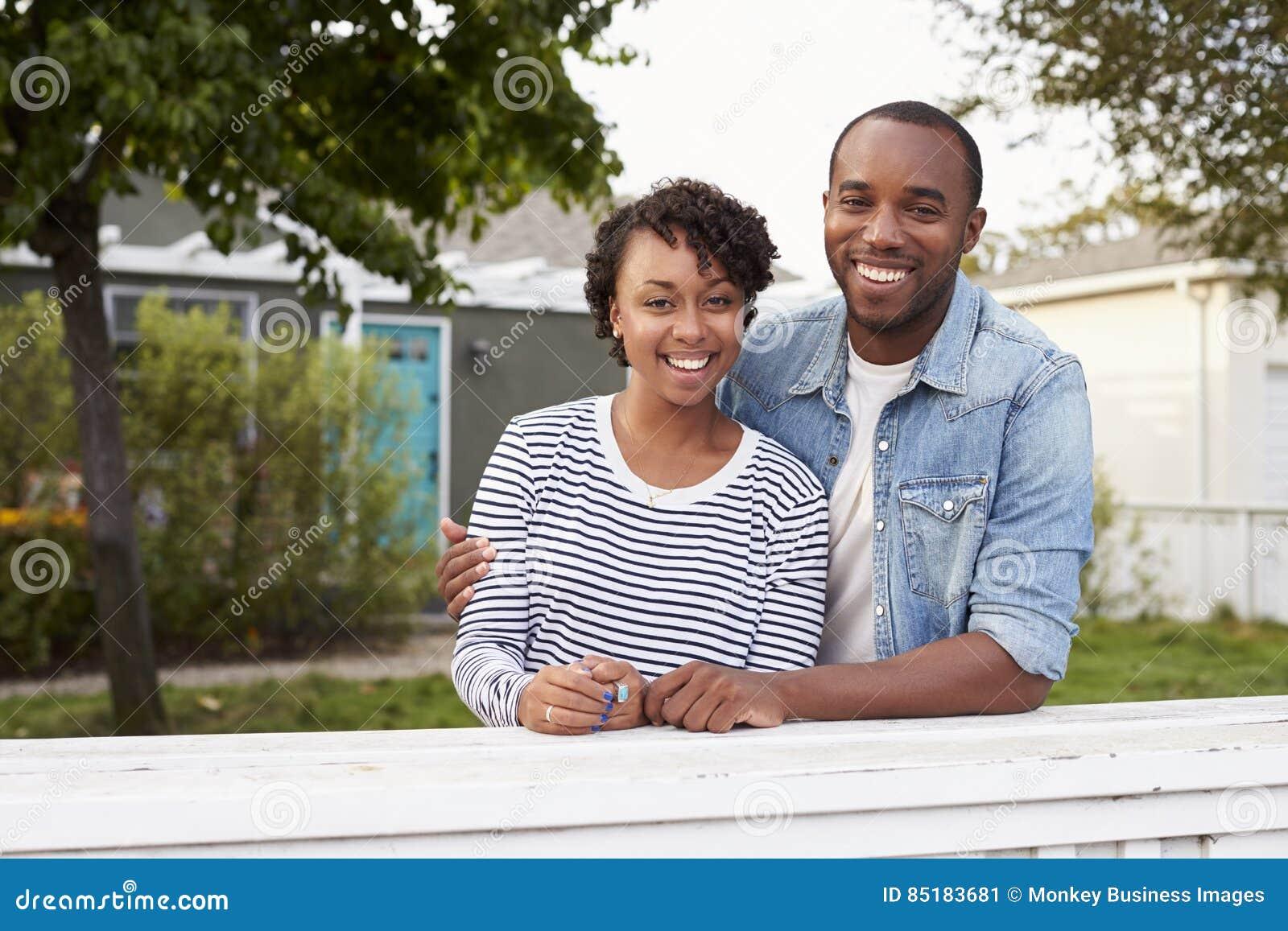 非裔美国人的夫妇看对照相机他们的房子外