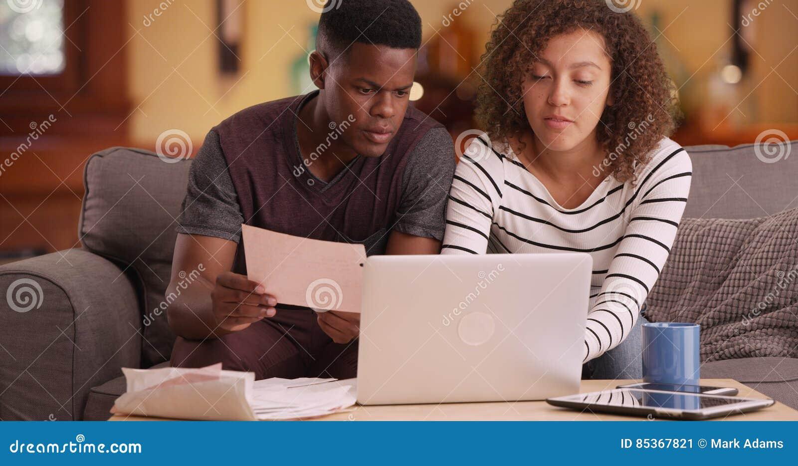 非裔美国人的夫妇付他们的在他们的膝上型计算机的帐单