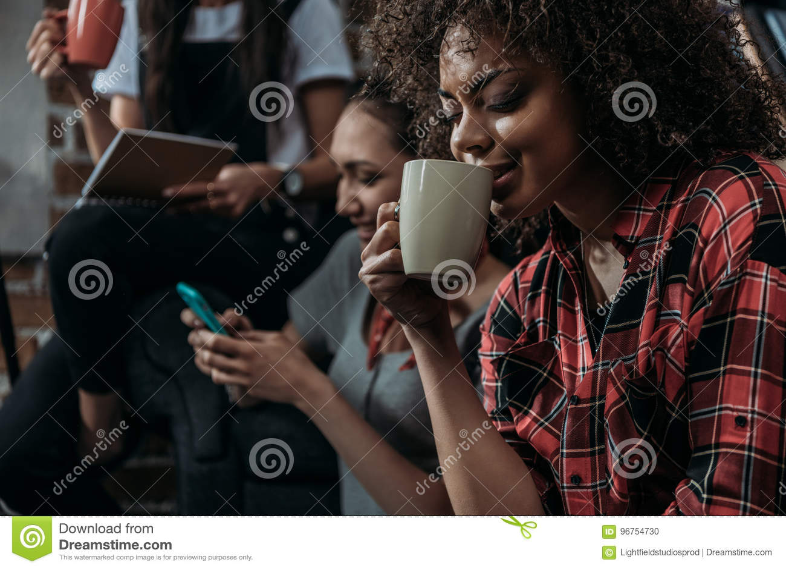 年轻非裔美国人的妇女饮用的咖啡,当使用智能手机的朋友和拿着杯子后边时