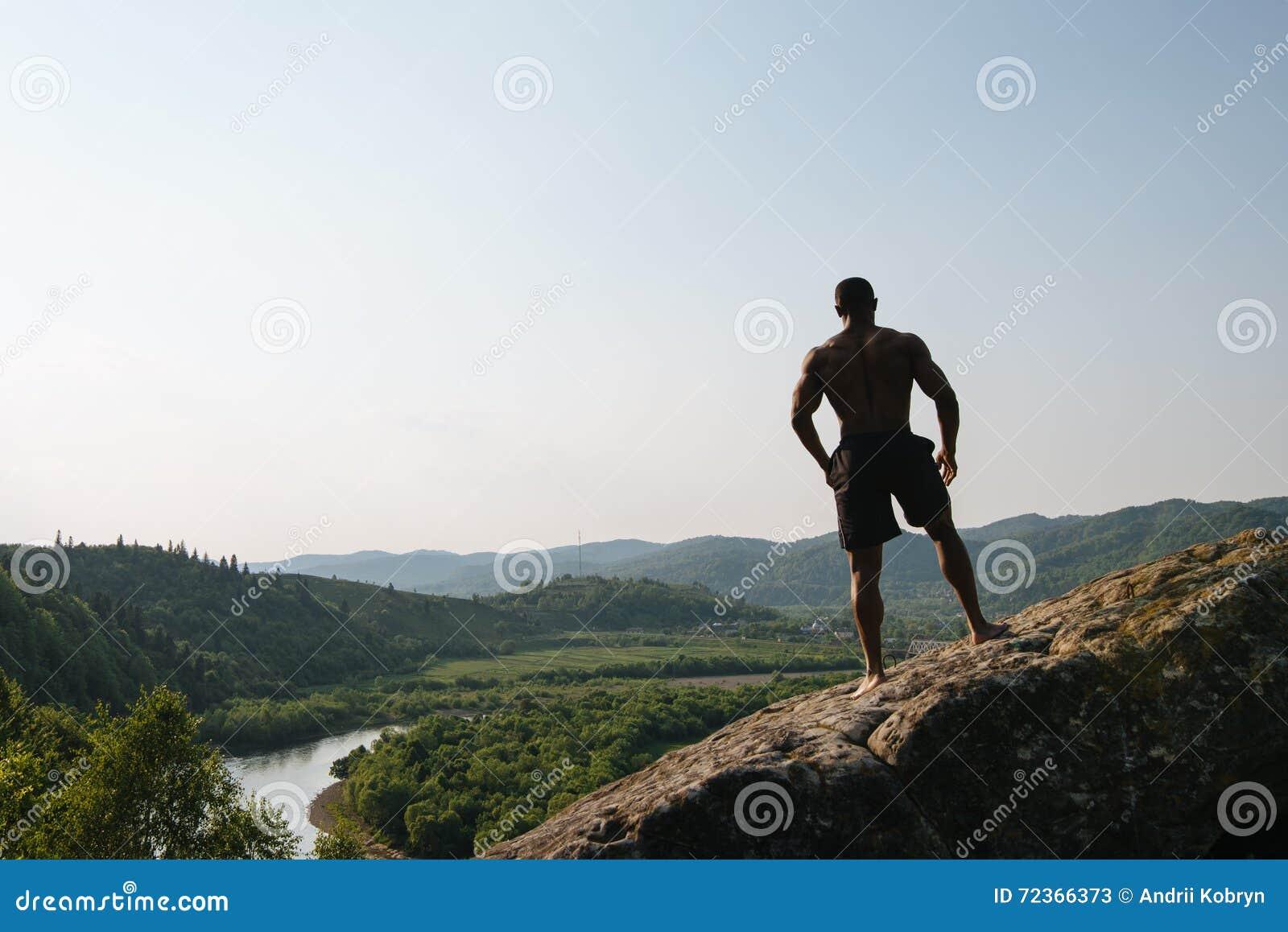 非裔美国人的运动人剪影有摆在岩石的赤裸躯干的 绿色山自然背景