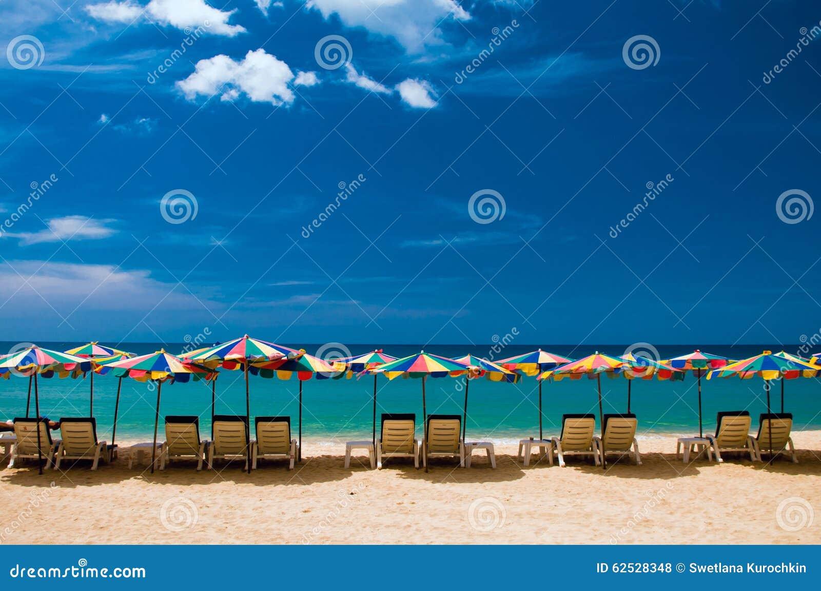 靠岸与白色沙子、椅子和umbrrellas 蓝色覆盖天空白色