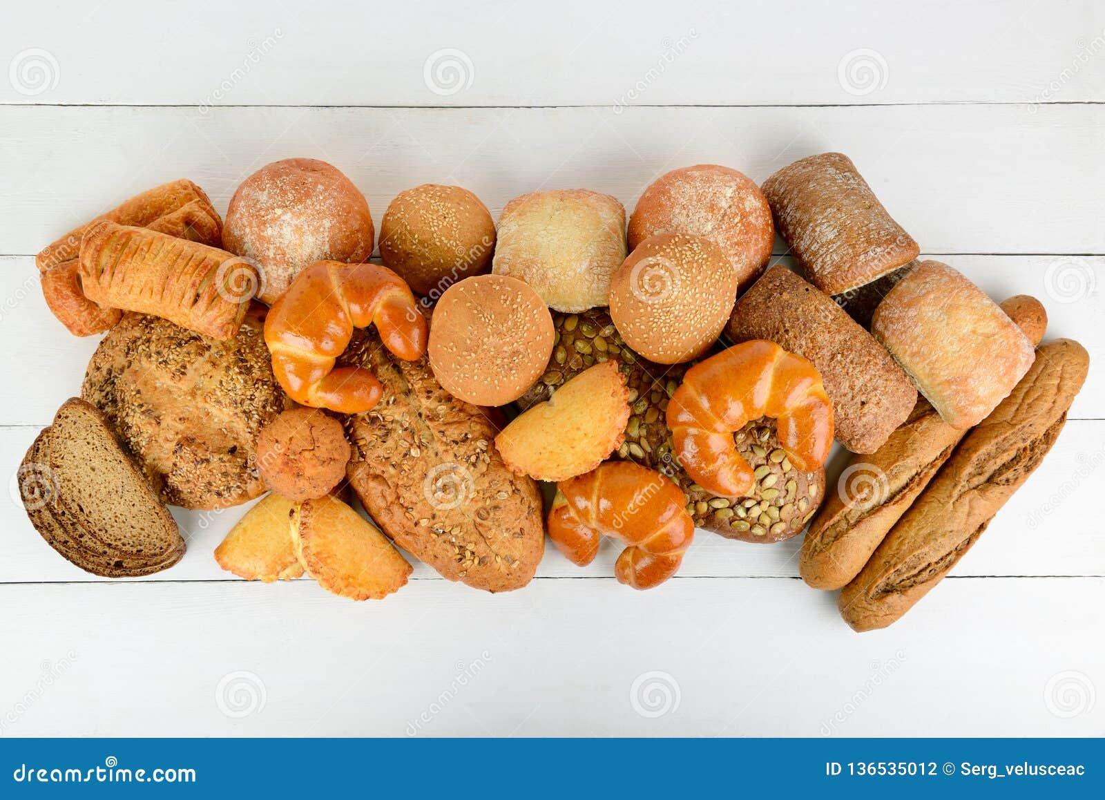 面包、小圆面包、新月形面包和其他焙烤食品在木桌上