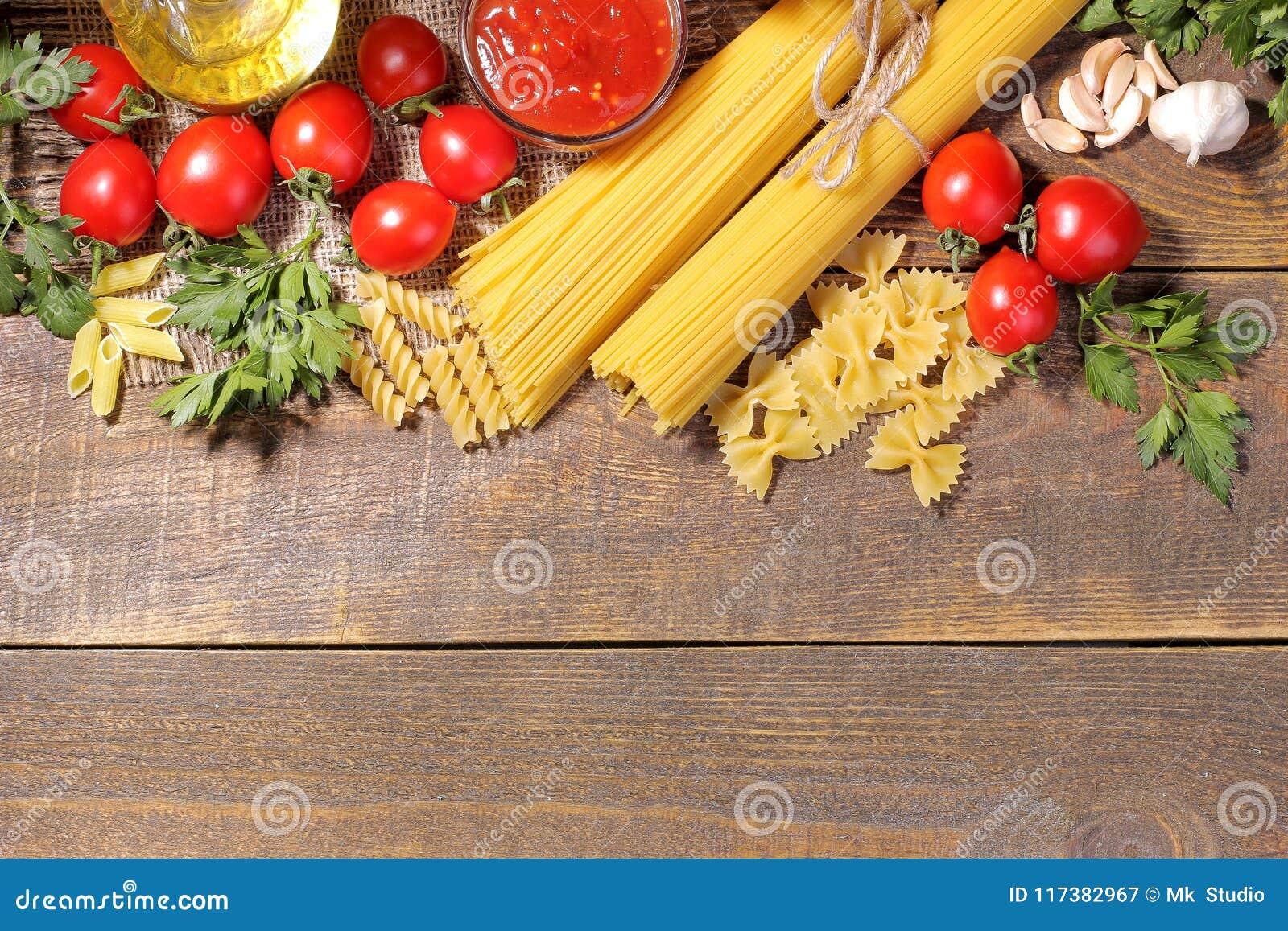 面团用西红柿,橄榄油,在棕色木背景的荷兰芹的不同的类型