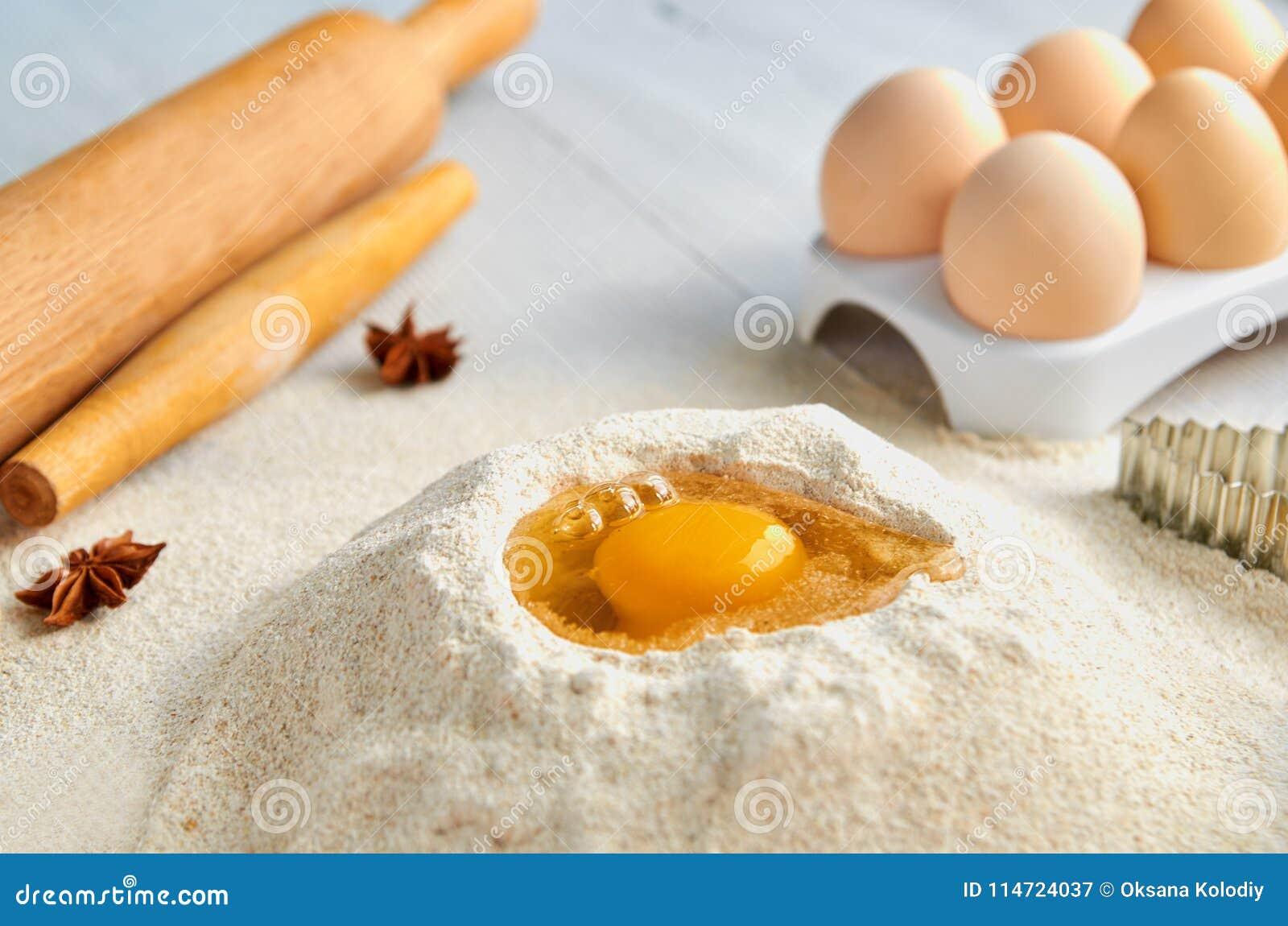面团食谱成份和辅助部件在灰色桌上:鸡蛋、面粉、香料和bakewares 烘烤背景
