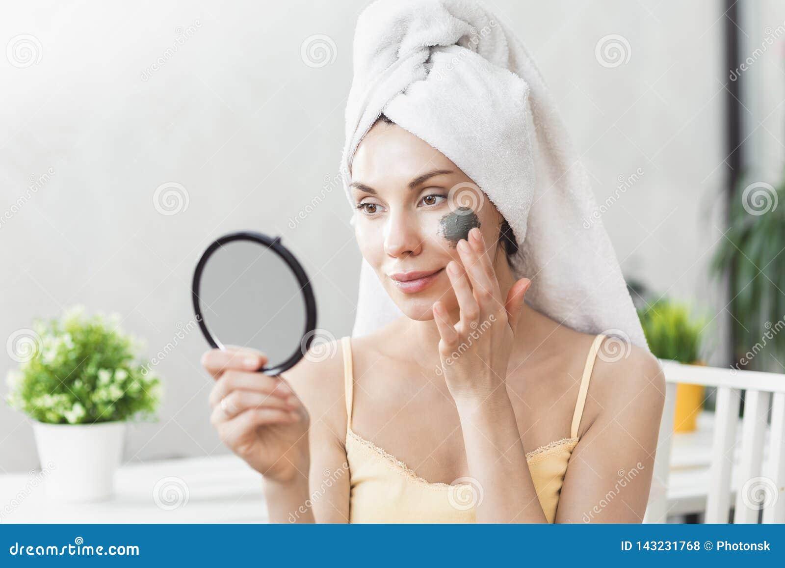 面孔护肤 在毛巾包裹的可爱的年轻女人,应用黏土泥面具面对 护肤概念 女孩