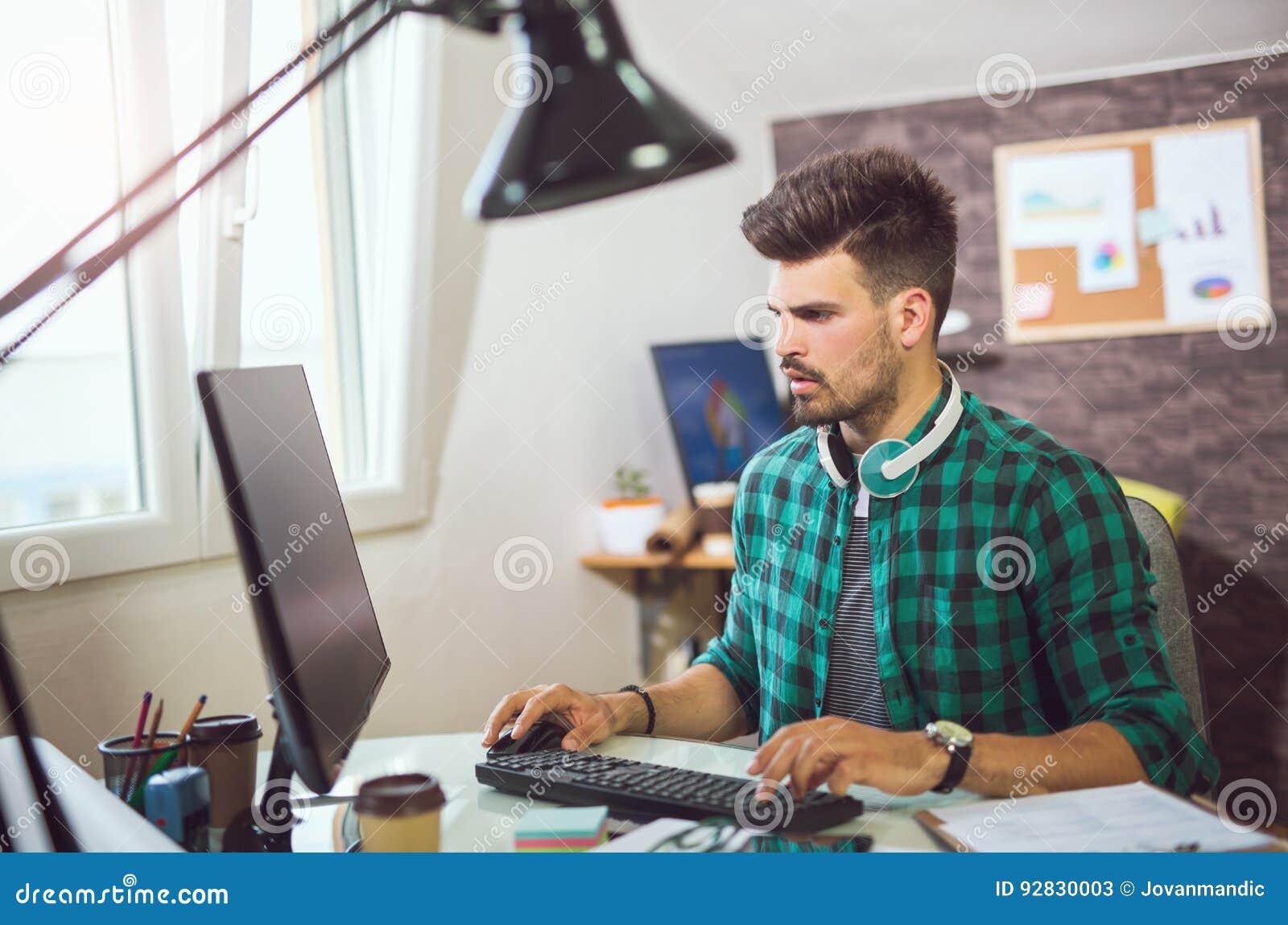 面对平面屏幕计算机的工作书桌的英俊的白种人人