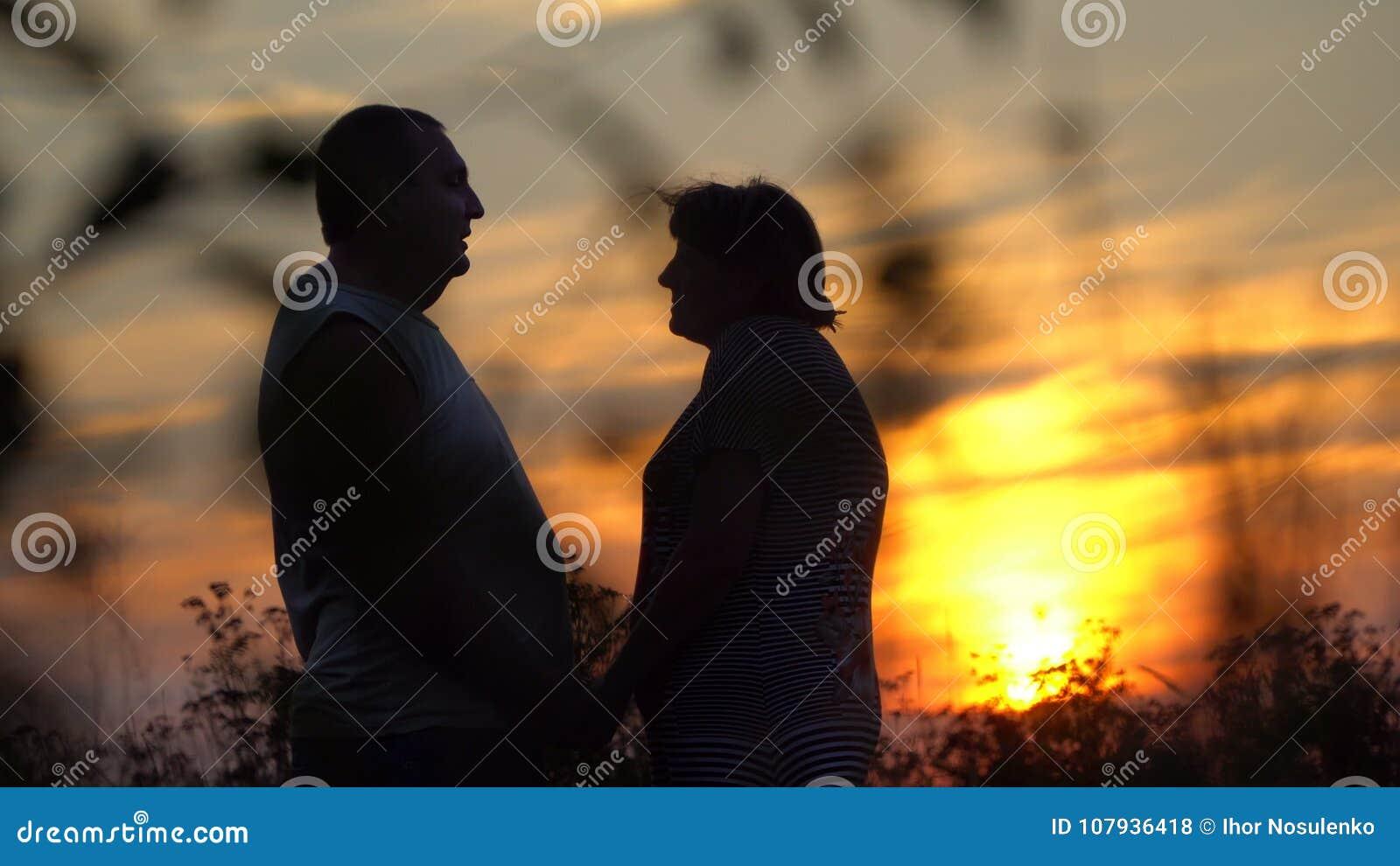 面对的男人和妇女在日落背景