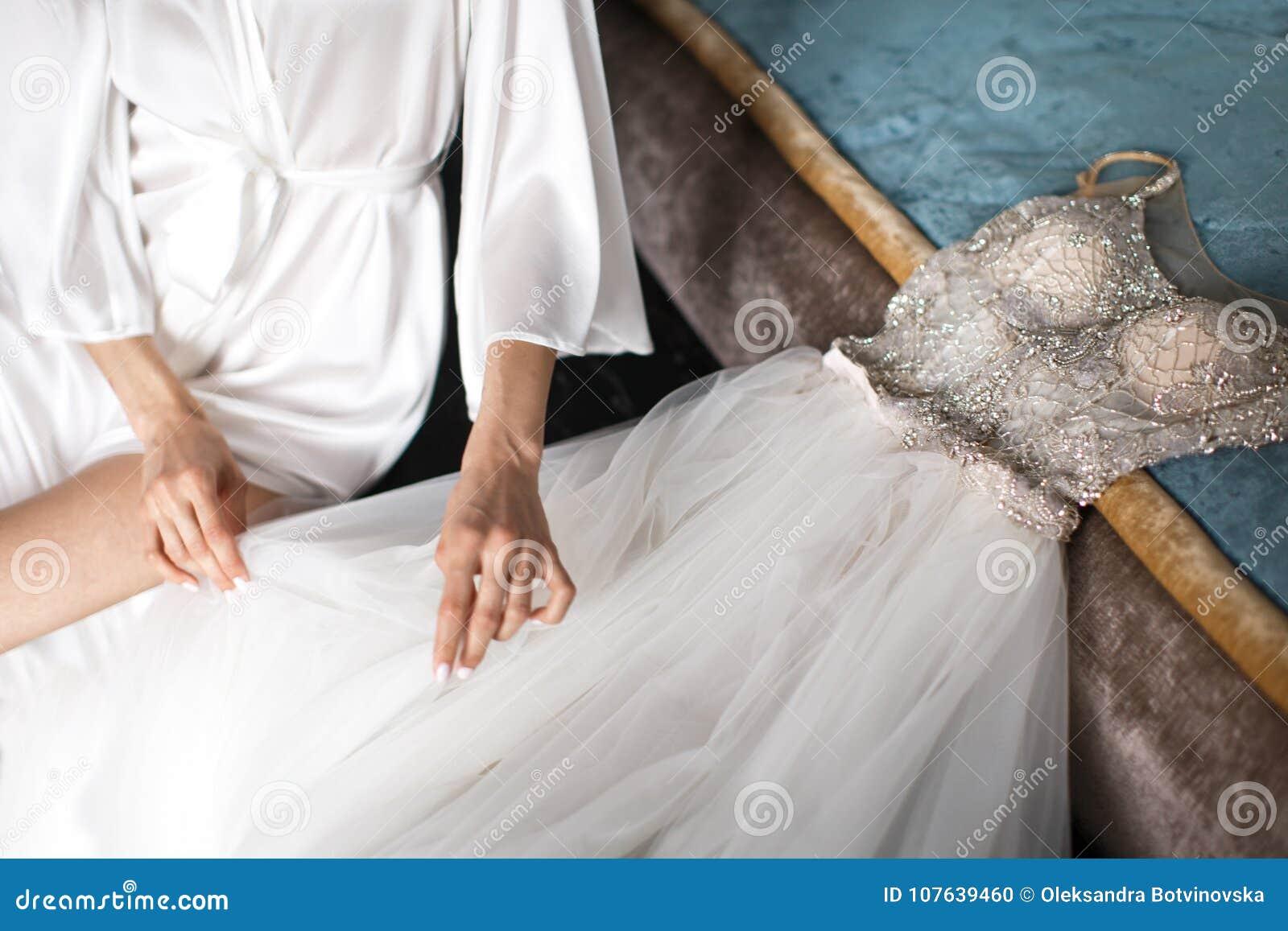 鞋带长袍和weding的礼服的新娘在床上