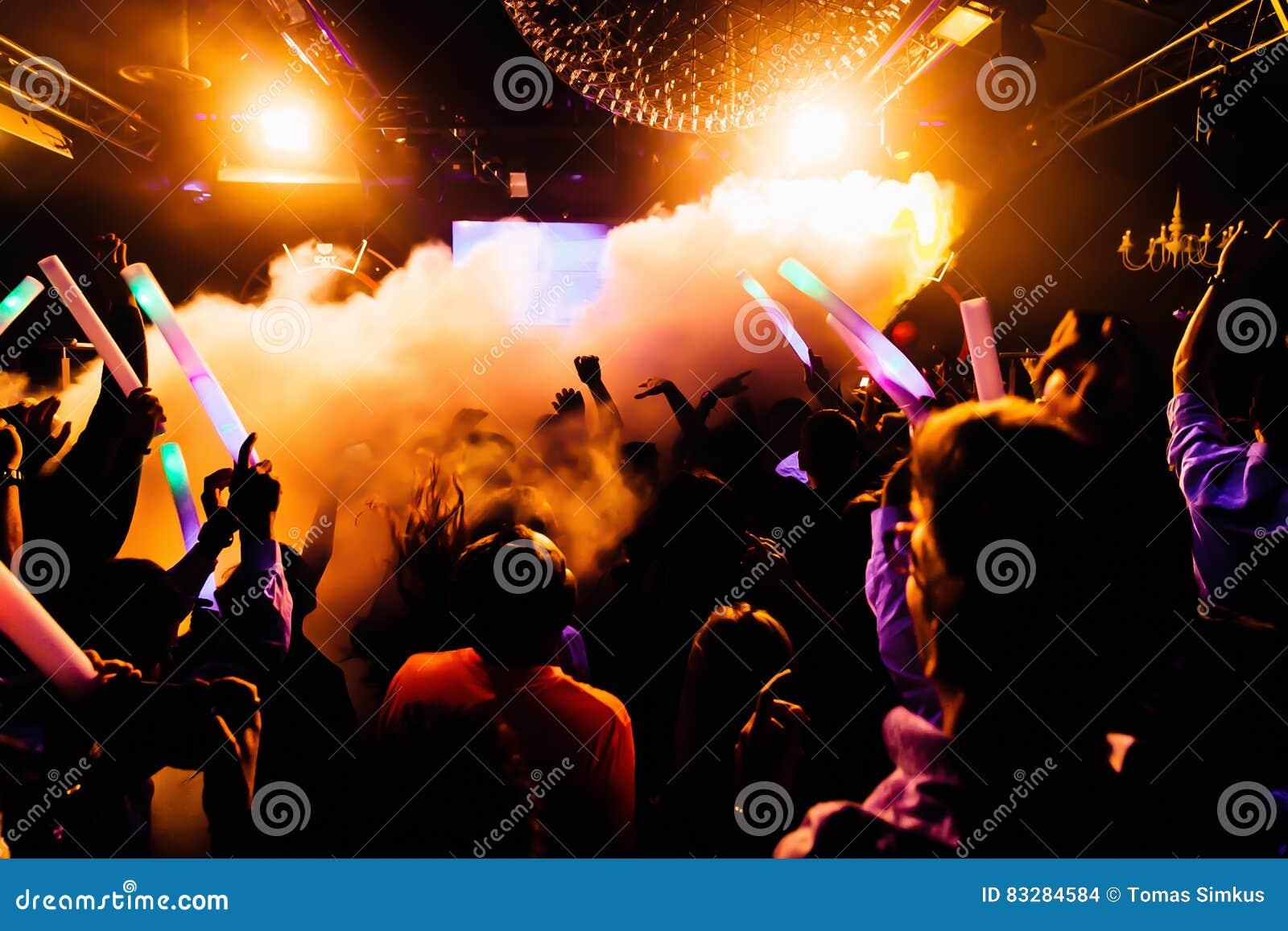 音乐会剪影在与五彩纸屑的明亮的阶段光前面拥挤