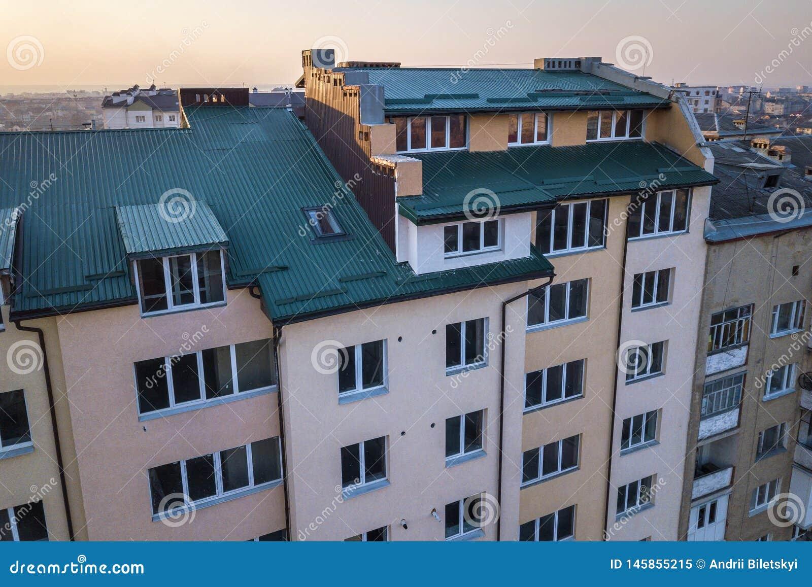 顶楼附录与塑料窗口、用绿色金属支持的板条盖的屋顶和墙壁的室外部鸟瞰图,新的天沟