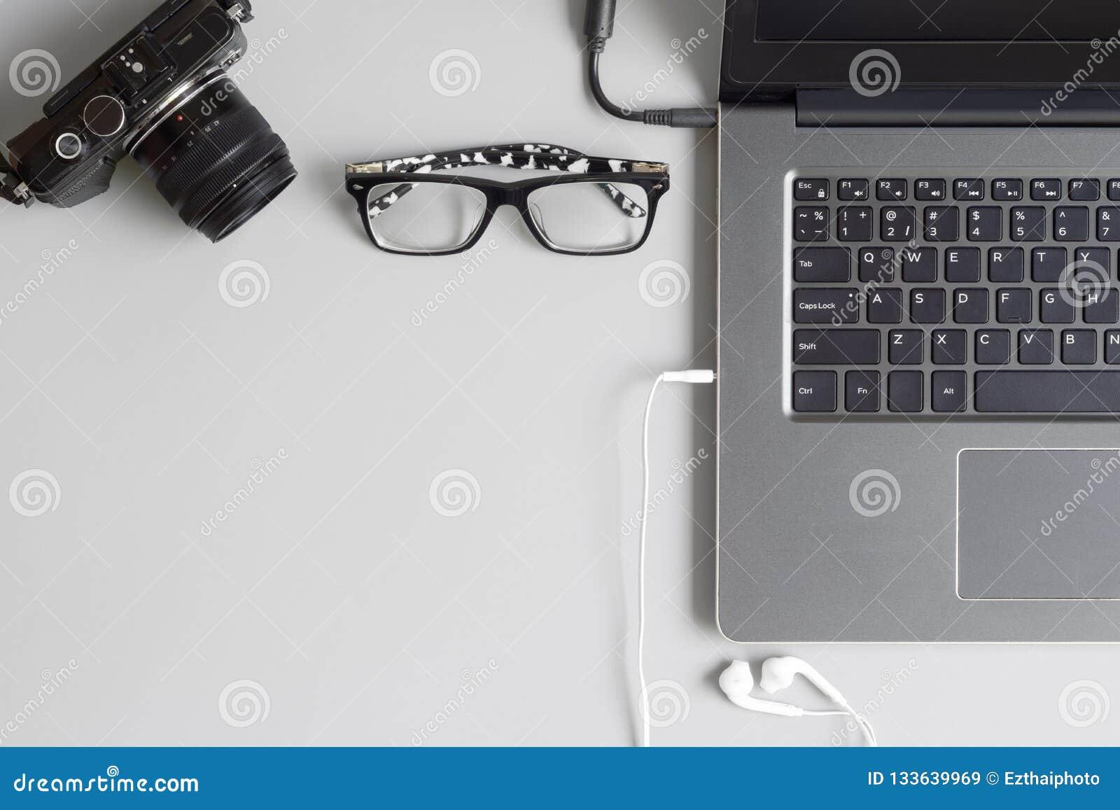 顶视图办公室与照相机、膝上型计算机笔记本、玻璃和耳机智能手机的桌概念在灰色桌背景 平的被放置的wi