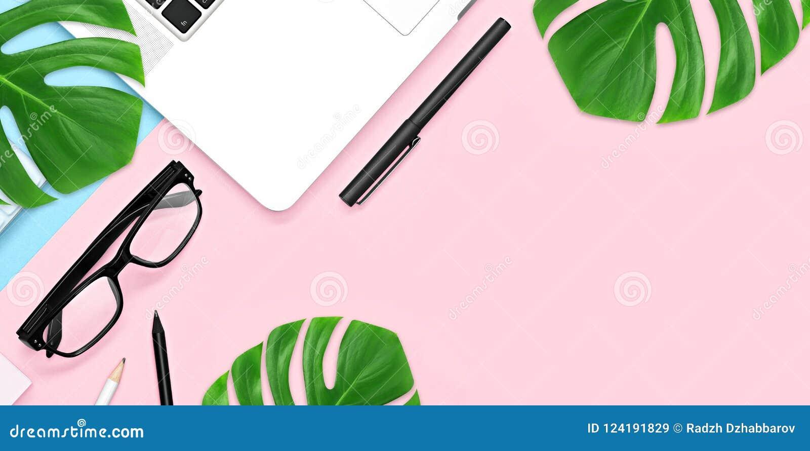 顶视图,办公室有拷贝空间的桌书桌 与绿色热带叶子和茶杯的工作区框架在蓝色桃红色背景