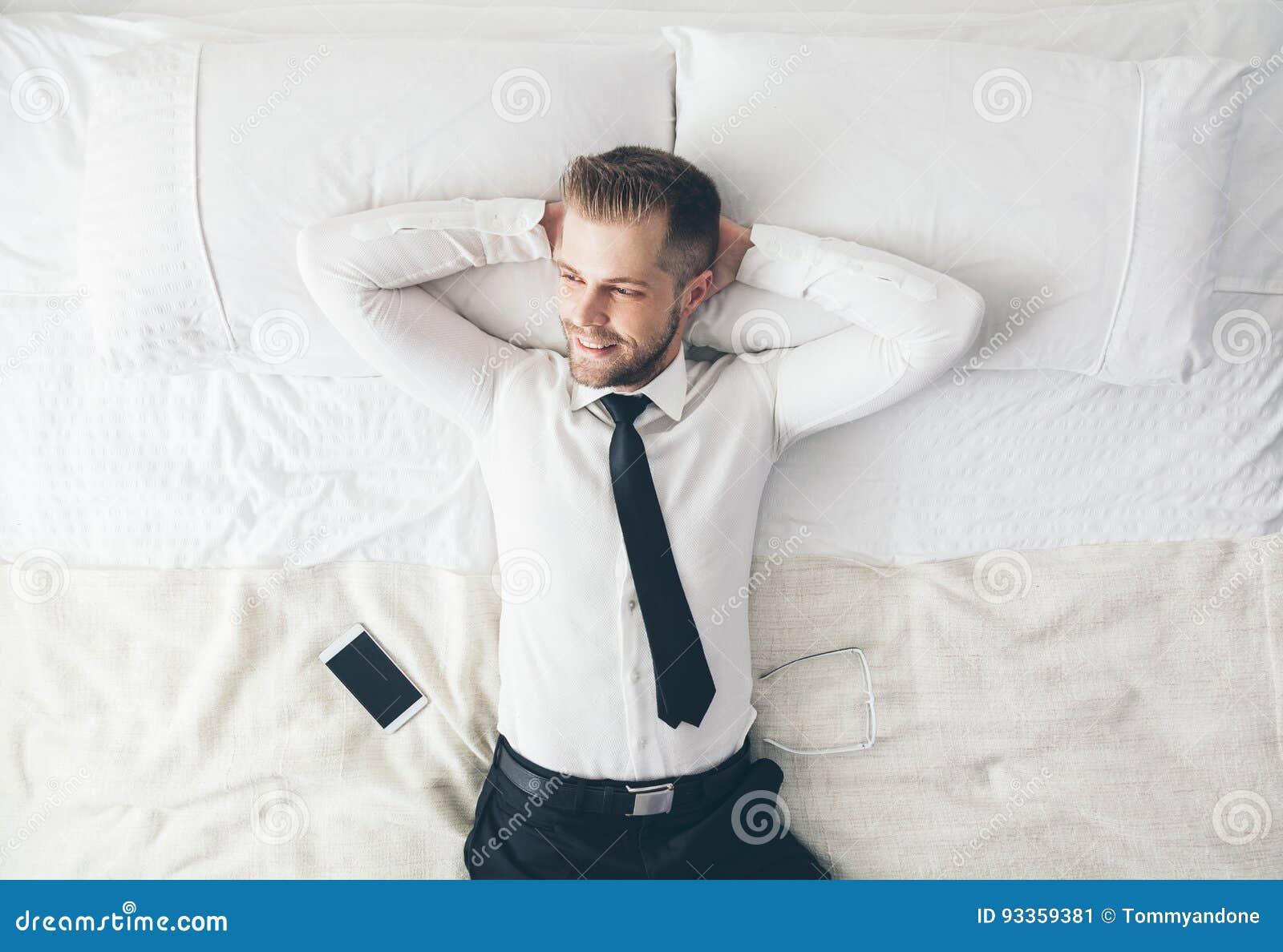 顶视图 放松在床上的英俊的商人在一困难的天以后在工作