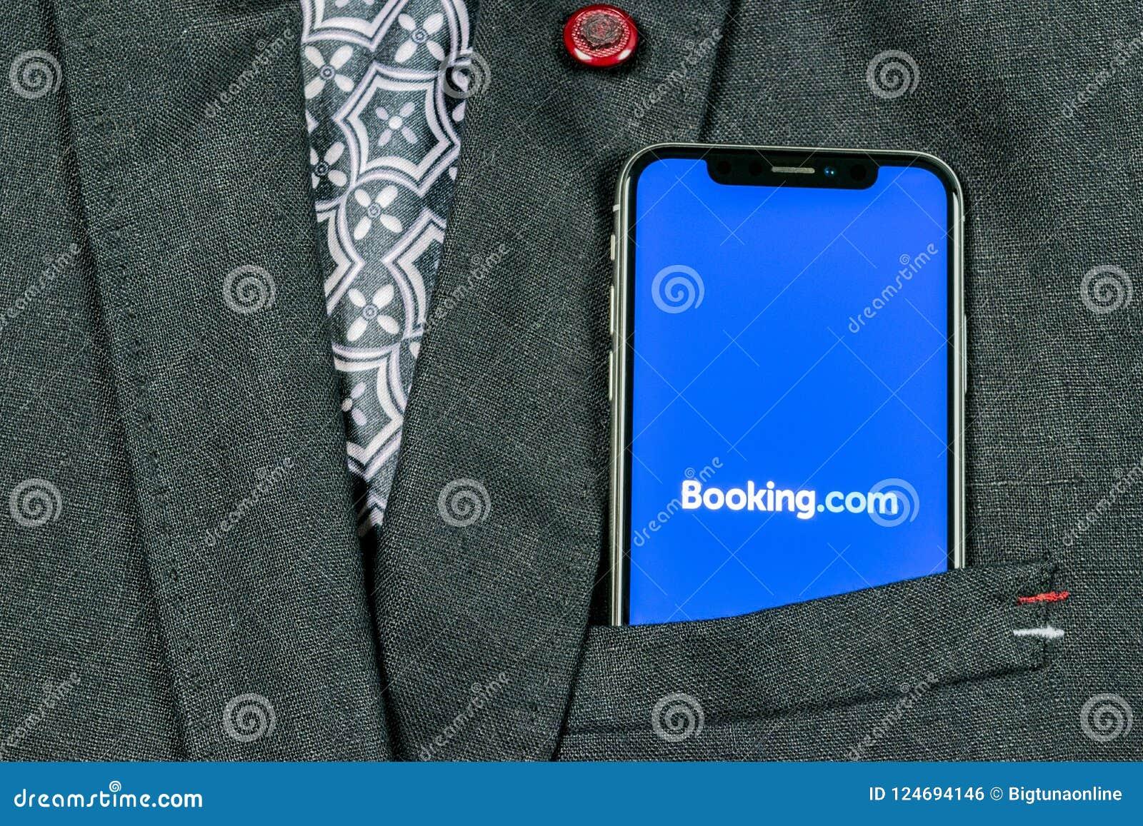 预订 com在苹果计算机iPhone x屏幕特写镜头的应用象在夹克口袋 售票app象 预订 com 社会媒介app