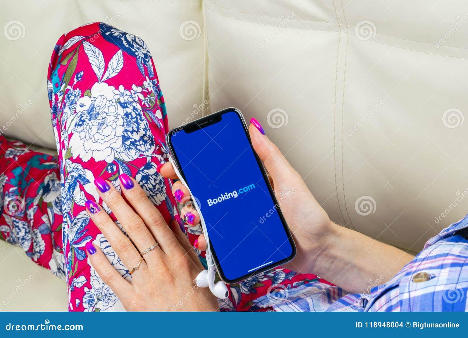 预订 com在苹果计算机iPhone x屏幕特写镜头的应用象在妇女手上 售票app象 预订 com 社会媒介app S