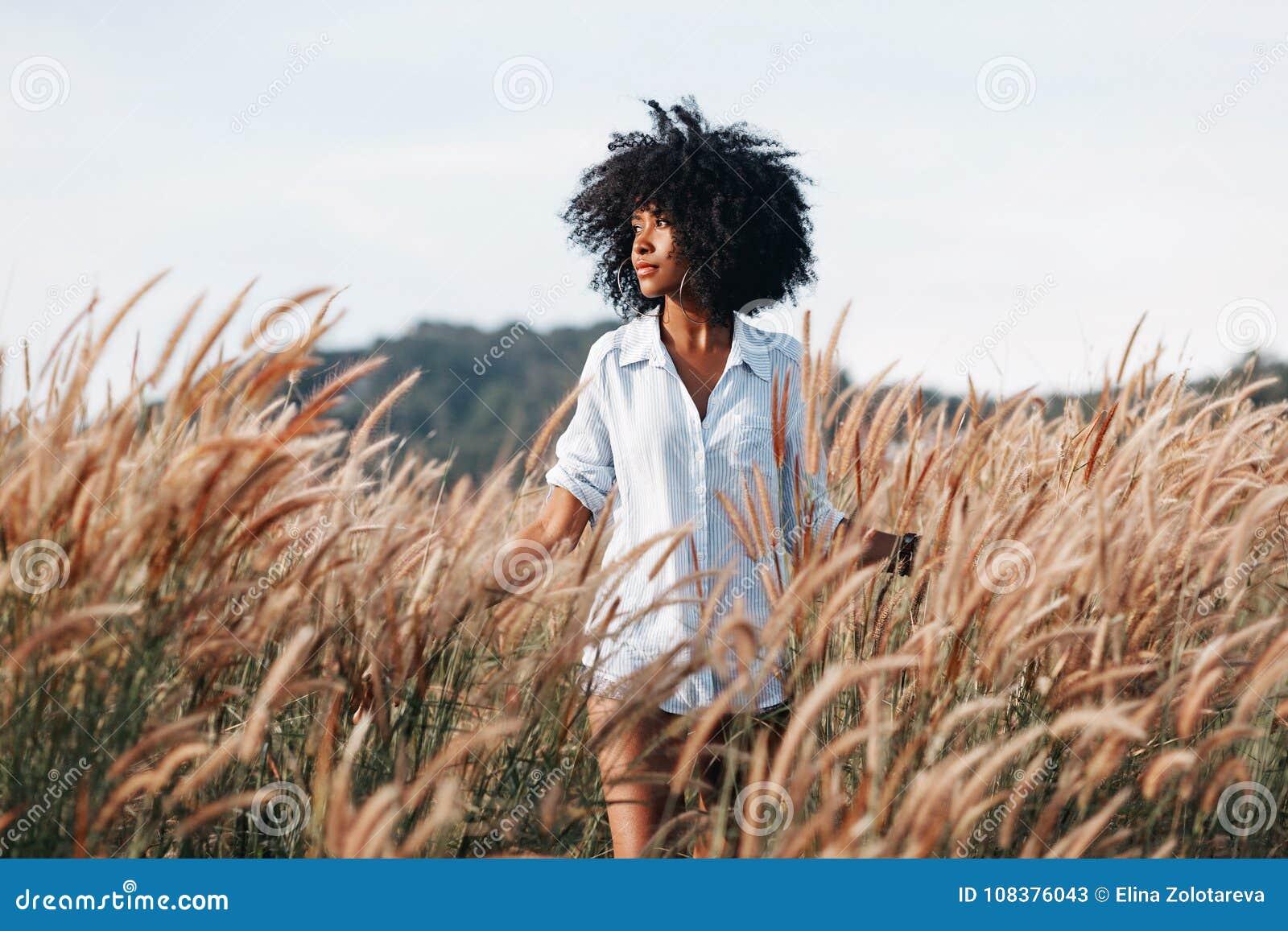 领域的快乐的非裔美国人的少妇在日落