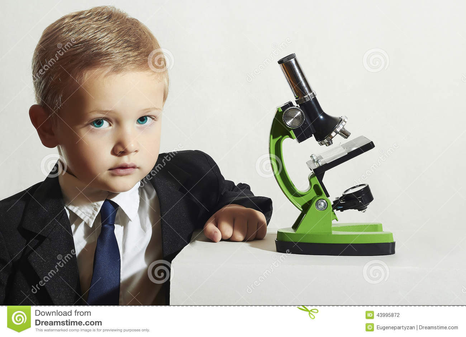 unusual制服 男小学生与显微镜一起使用 聪明的男孩 科学.图片