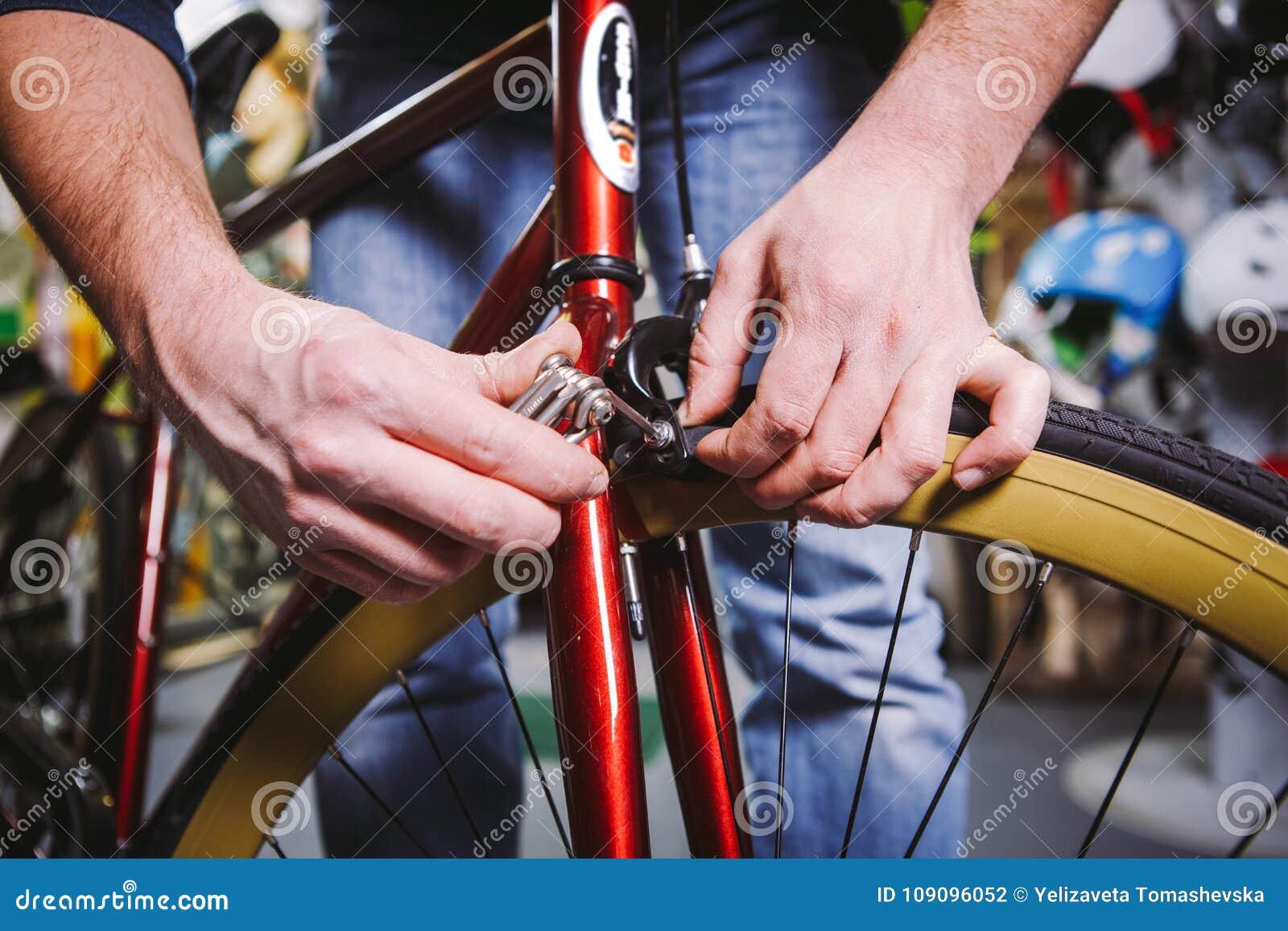 题材修理自行车 一个白种人人` s手用途的特写镜头手工工具六角形集合调整和安装外缘闸在一红色bicy