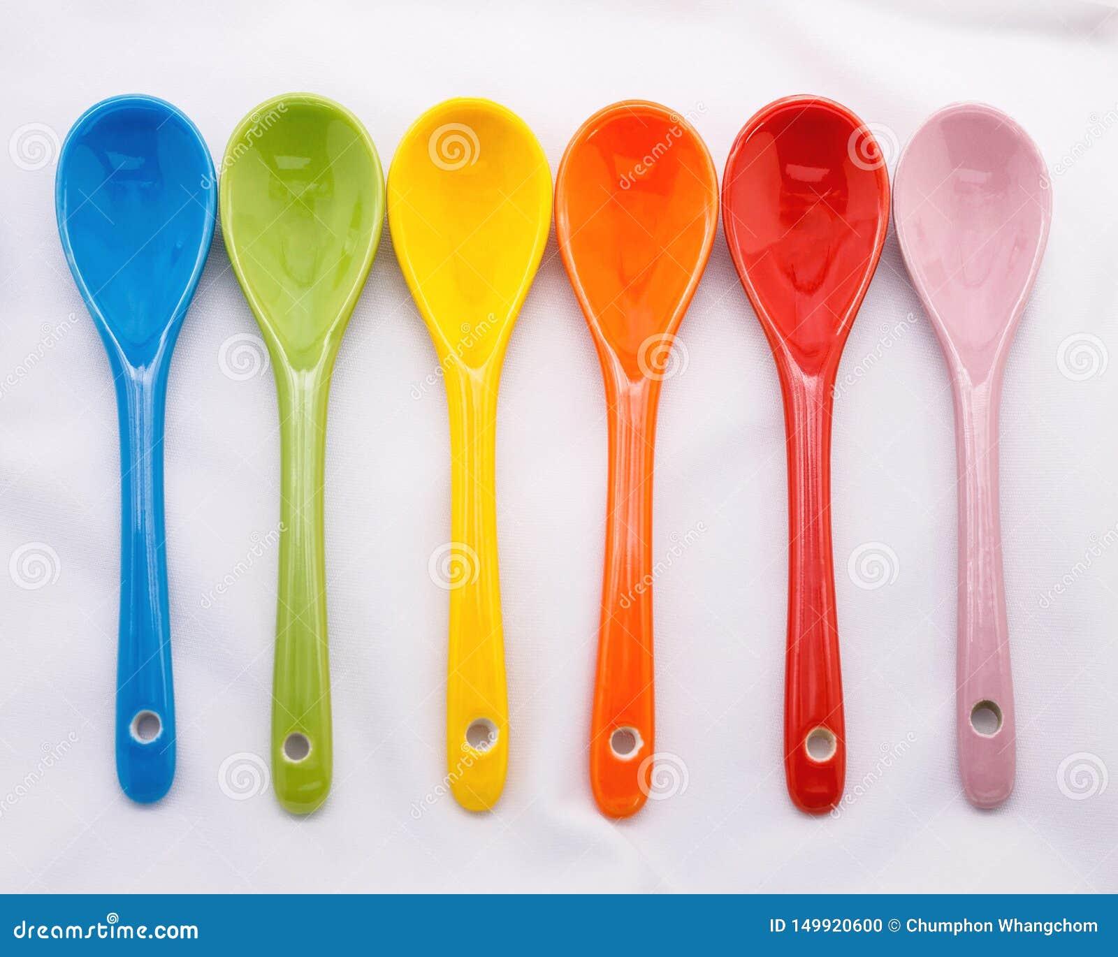 颜色在白色织品背景的陶瓷匙子 五颜六色的概念