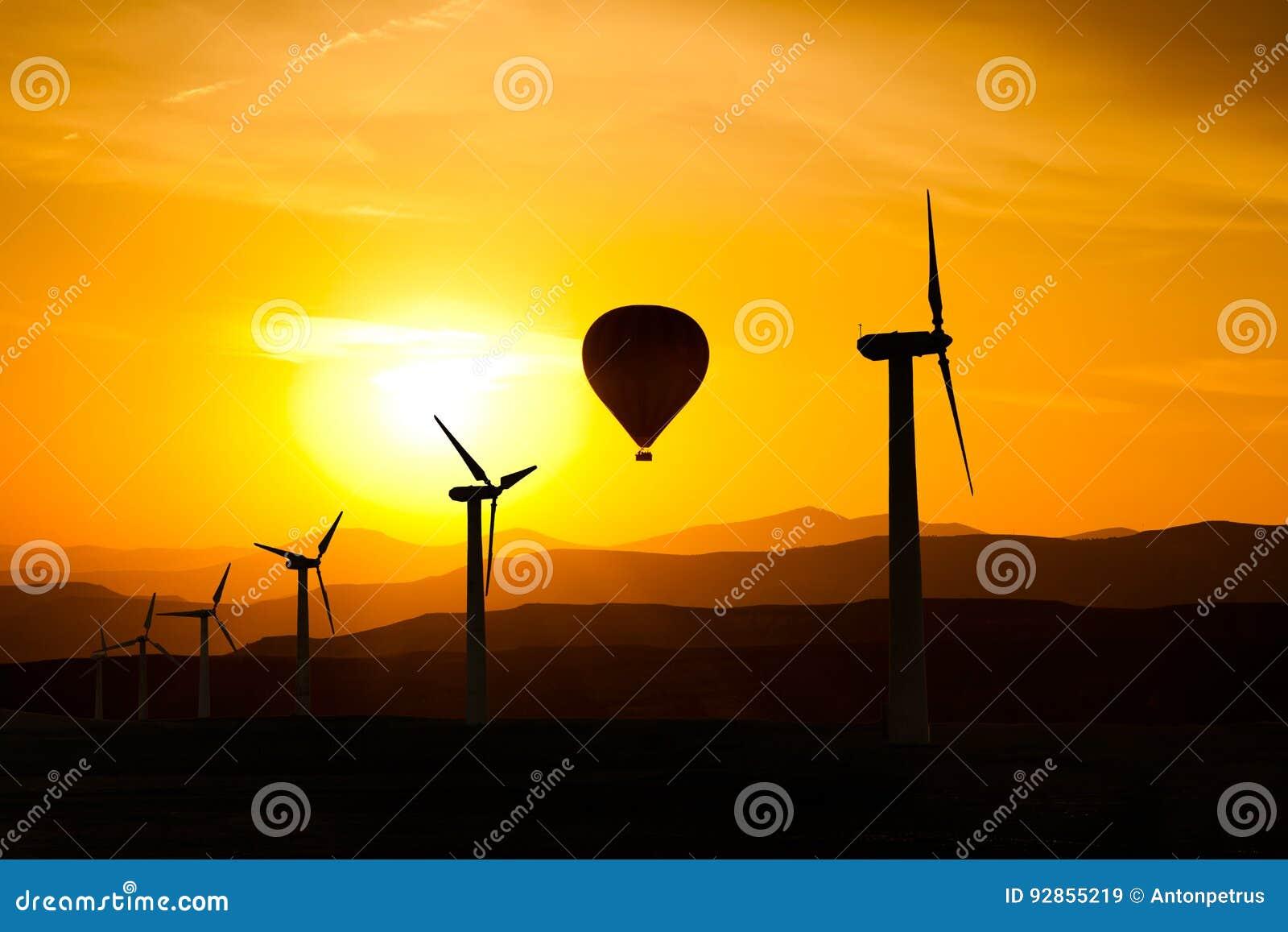 风轮机剪影和一个热空气迅速增加f山和日落